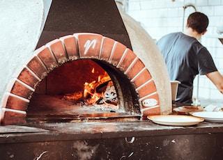 man standing beside fireplace facing backwards