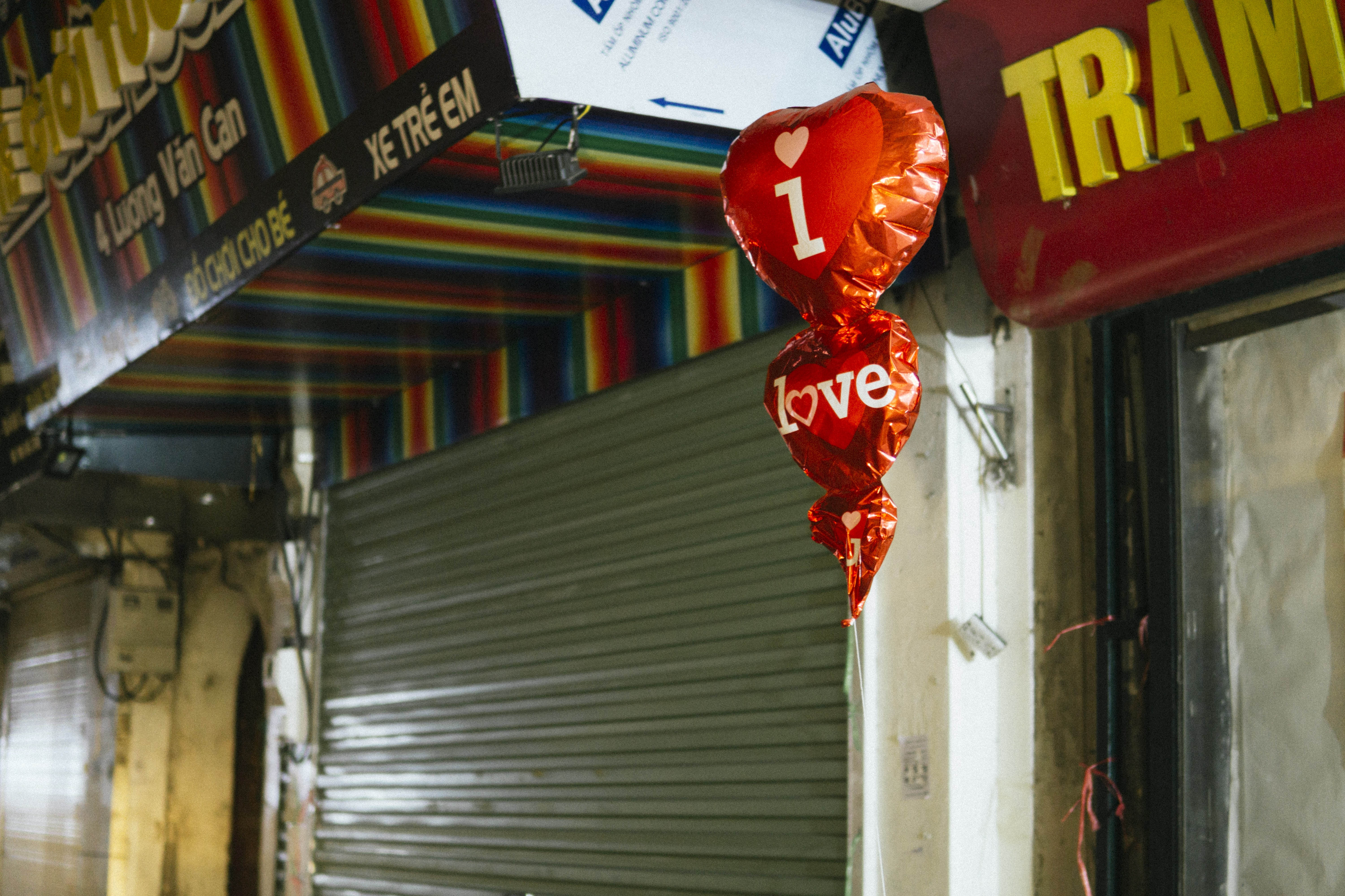 """3 helium balloons near closed businesses read """"I love you,"""" but one has deflated."""
