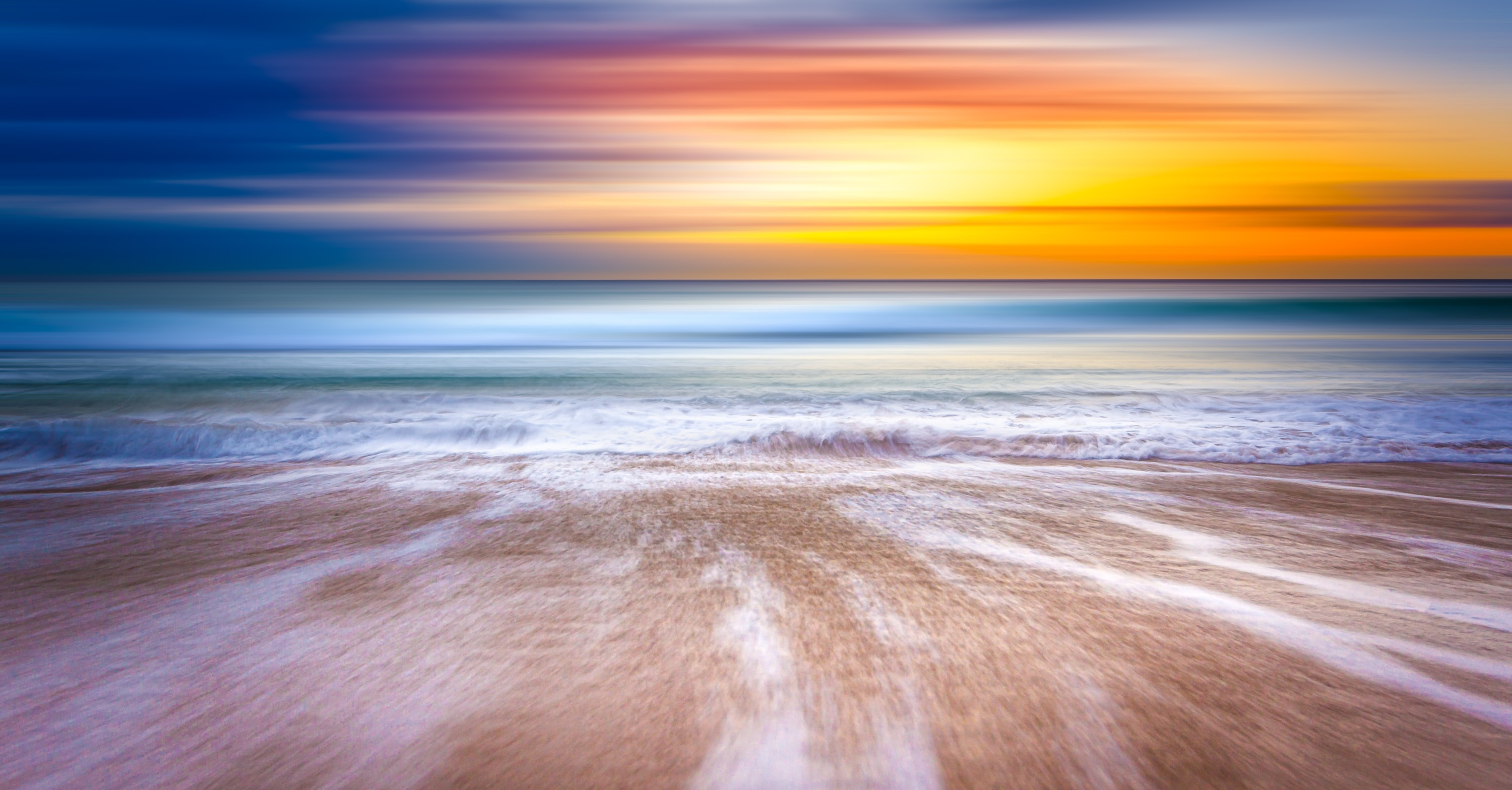 A colorful shot of a blurry shoreline on a Sydney beach, with a sunset in the horizon