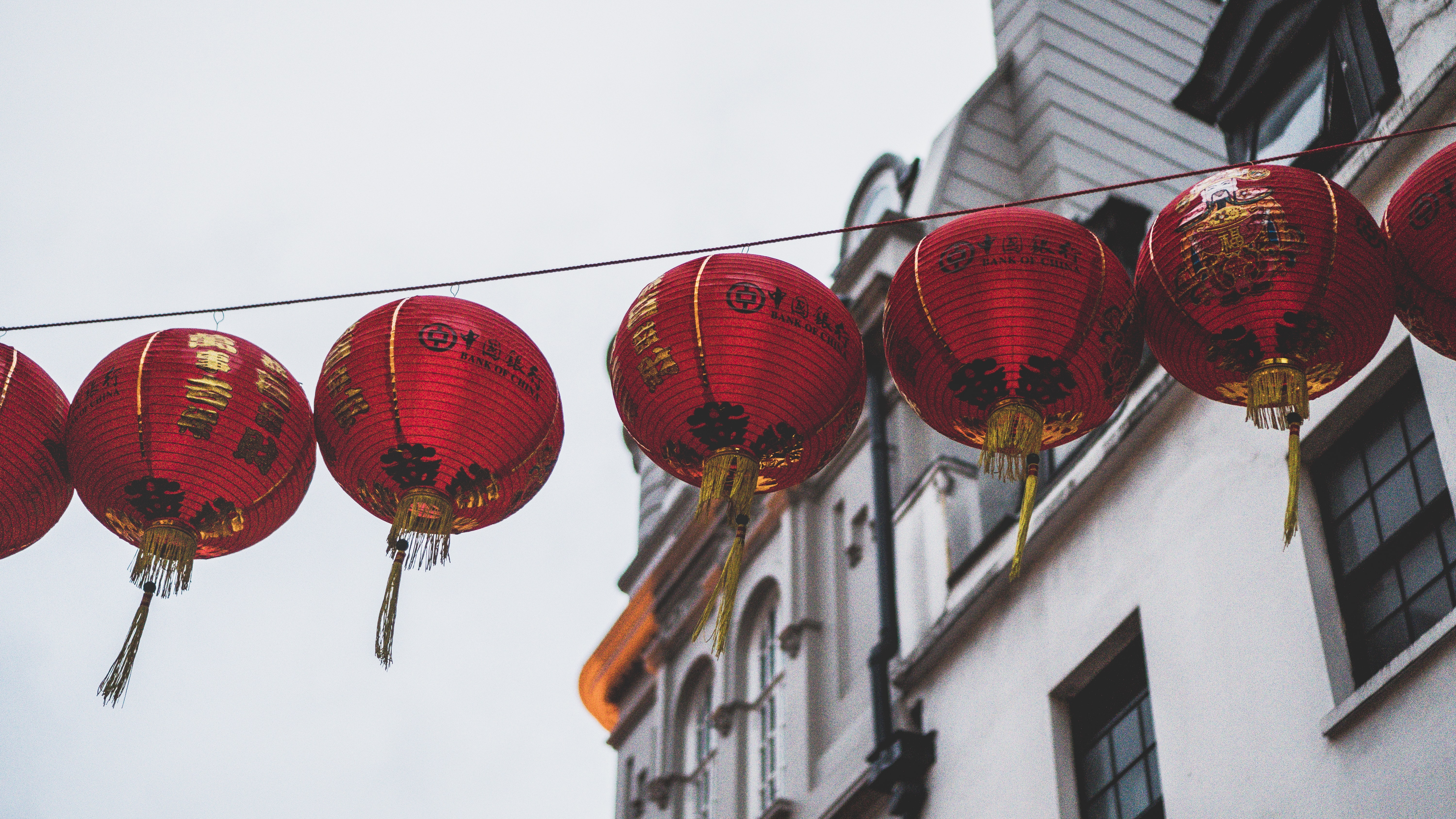 Row of red Chinese lanterns hanging above a street.