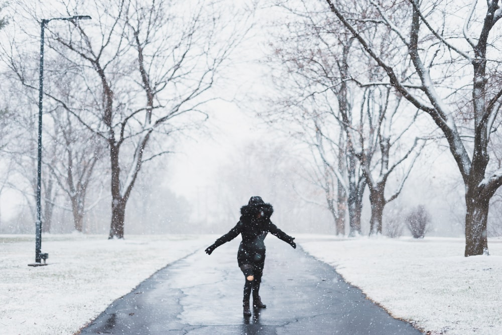 woman wearing black parka jacket standing on road near tall trees and light post during daytime