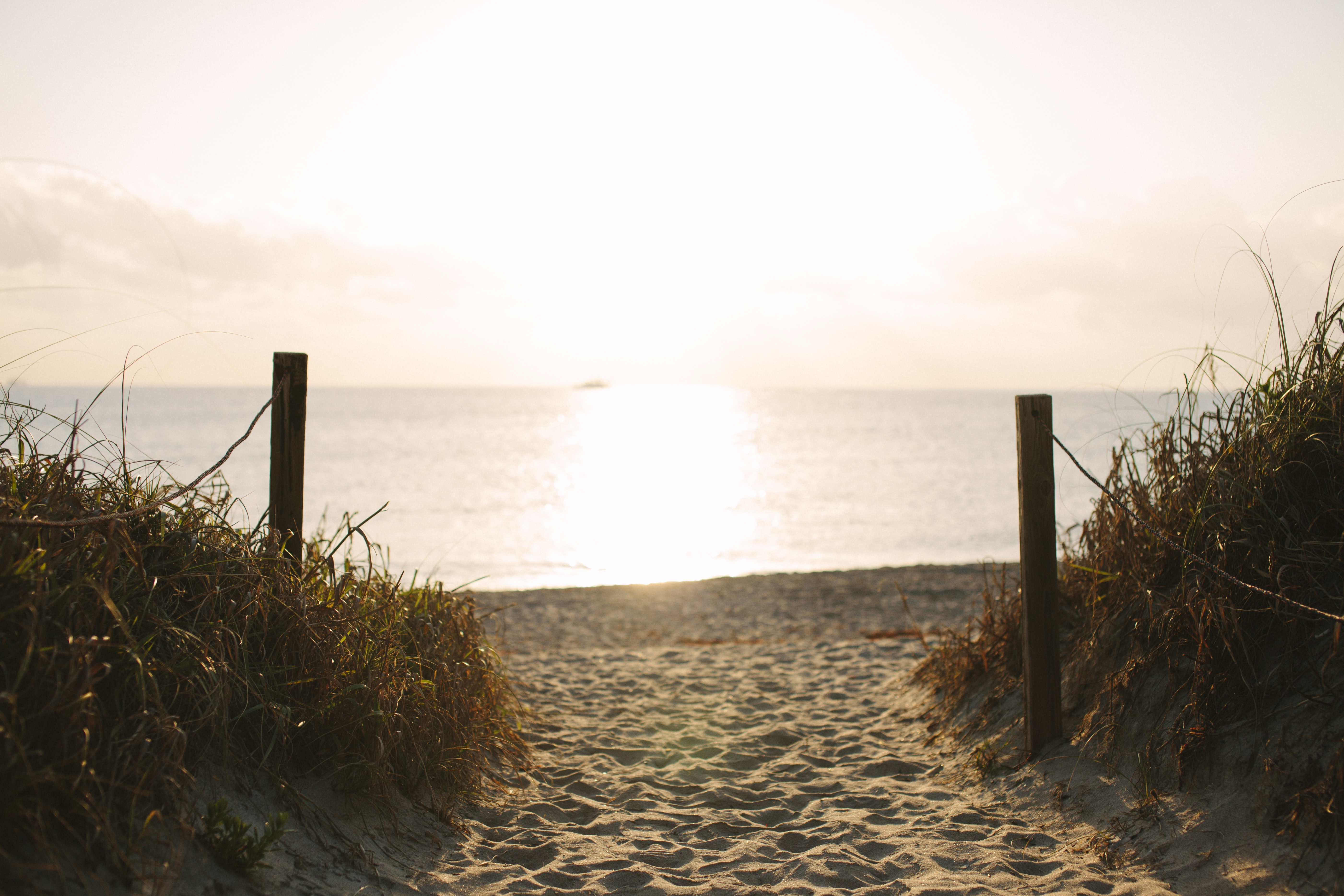 Rope fenced path leading to the fine sand beach at sunset