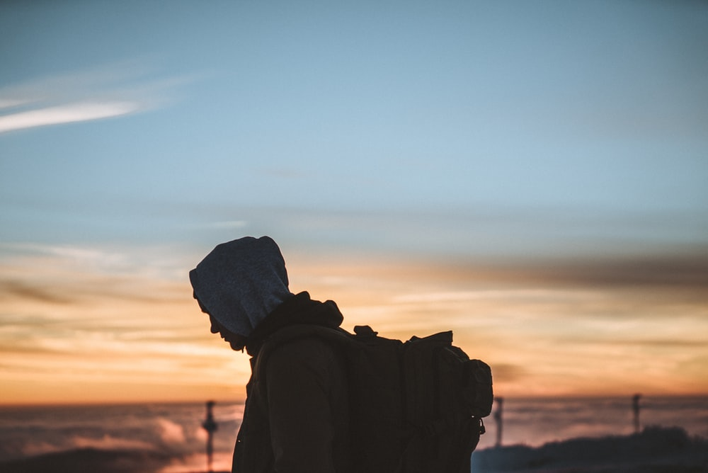 silhouette of person carrying backpack during orange sunset