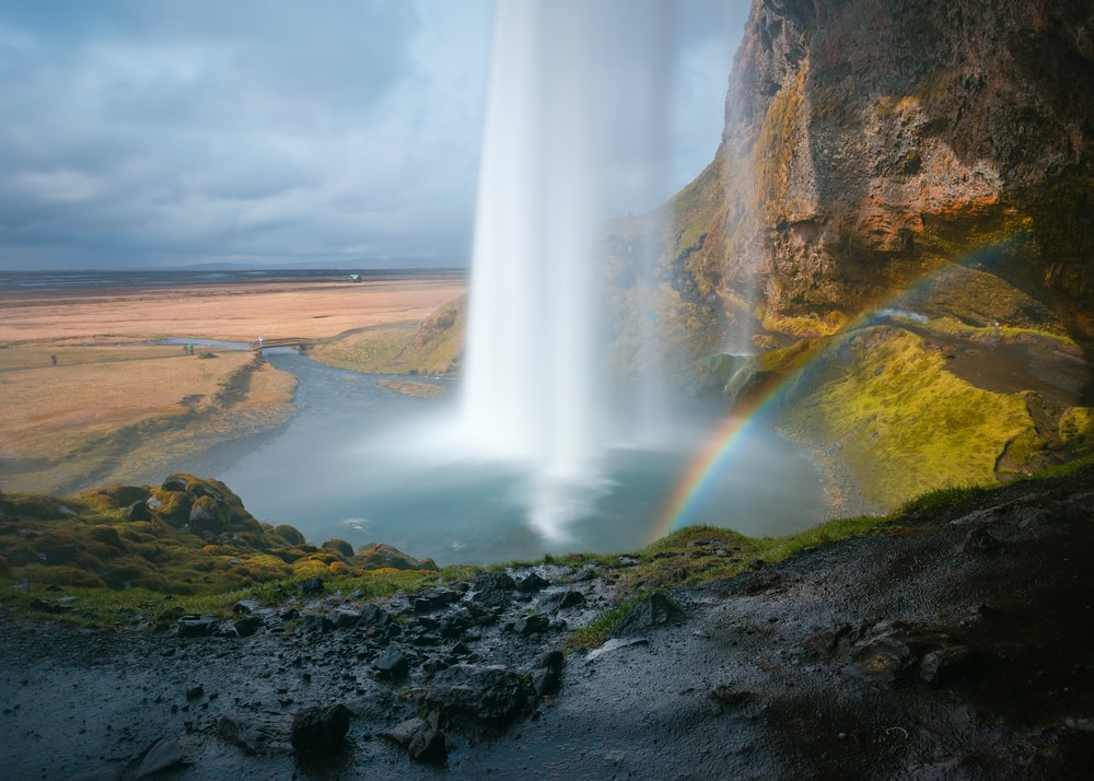 waterfall under grey sky