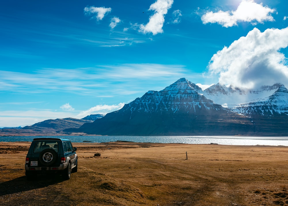 SUV parking on brown field facing lake across snow capped black mountain at daytime