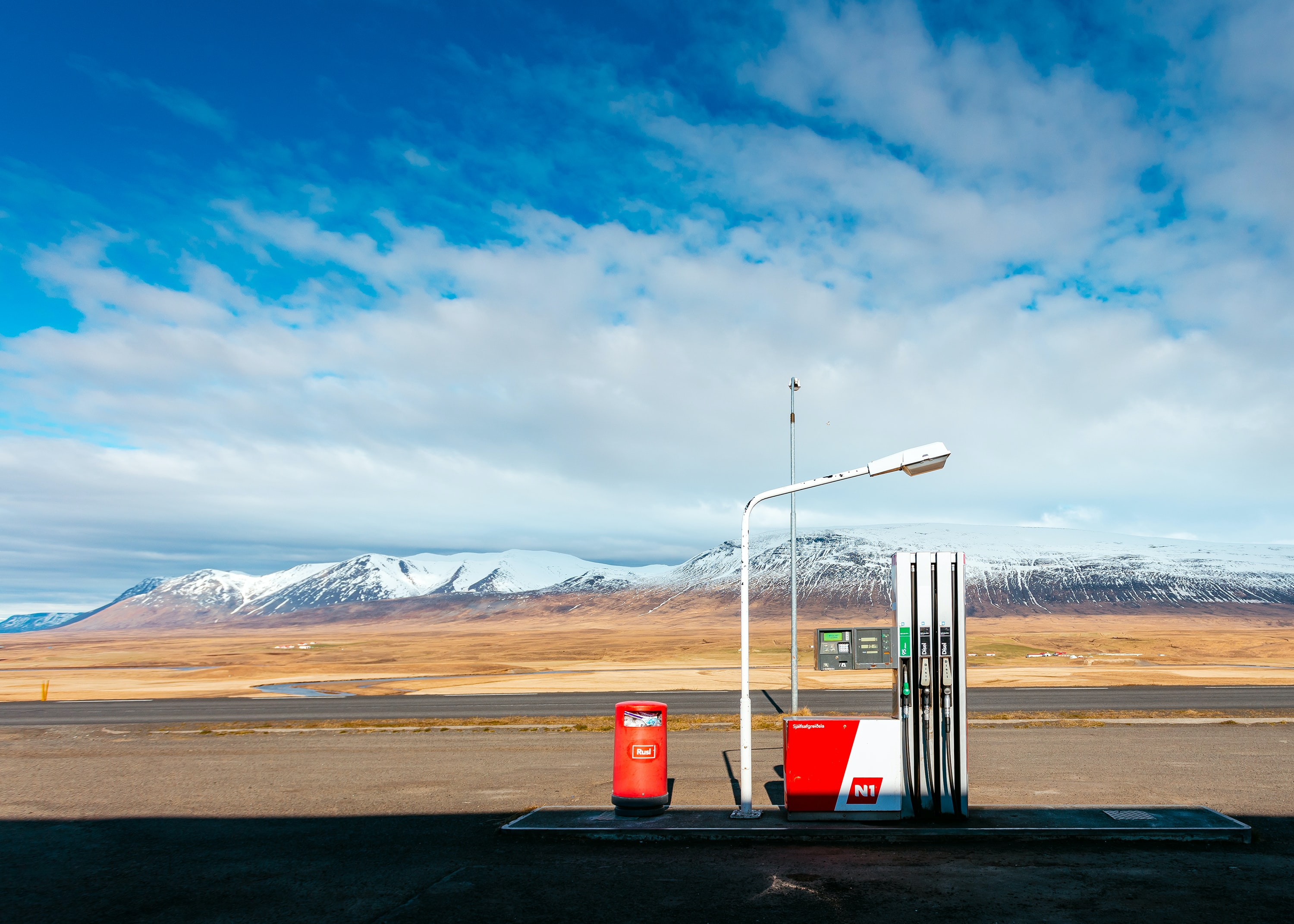 empty gas station near empty road facing snow capped mountain at daytime