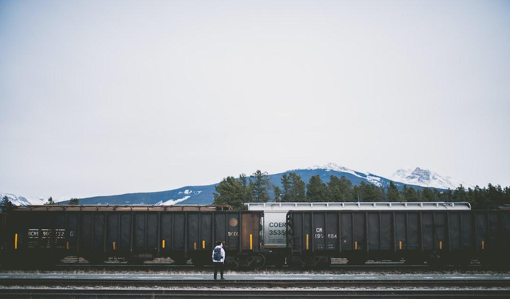 man standing on railroad near train