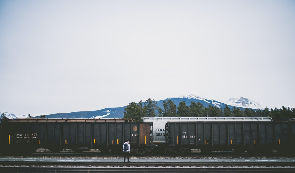 man standing on railroad near train