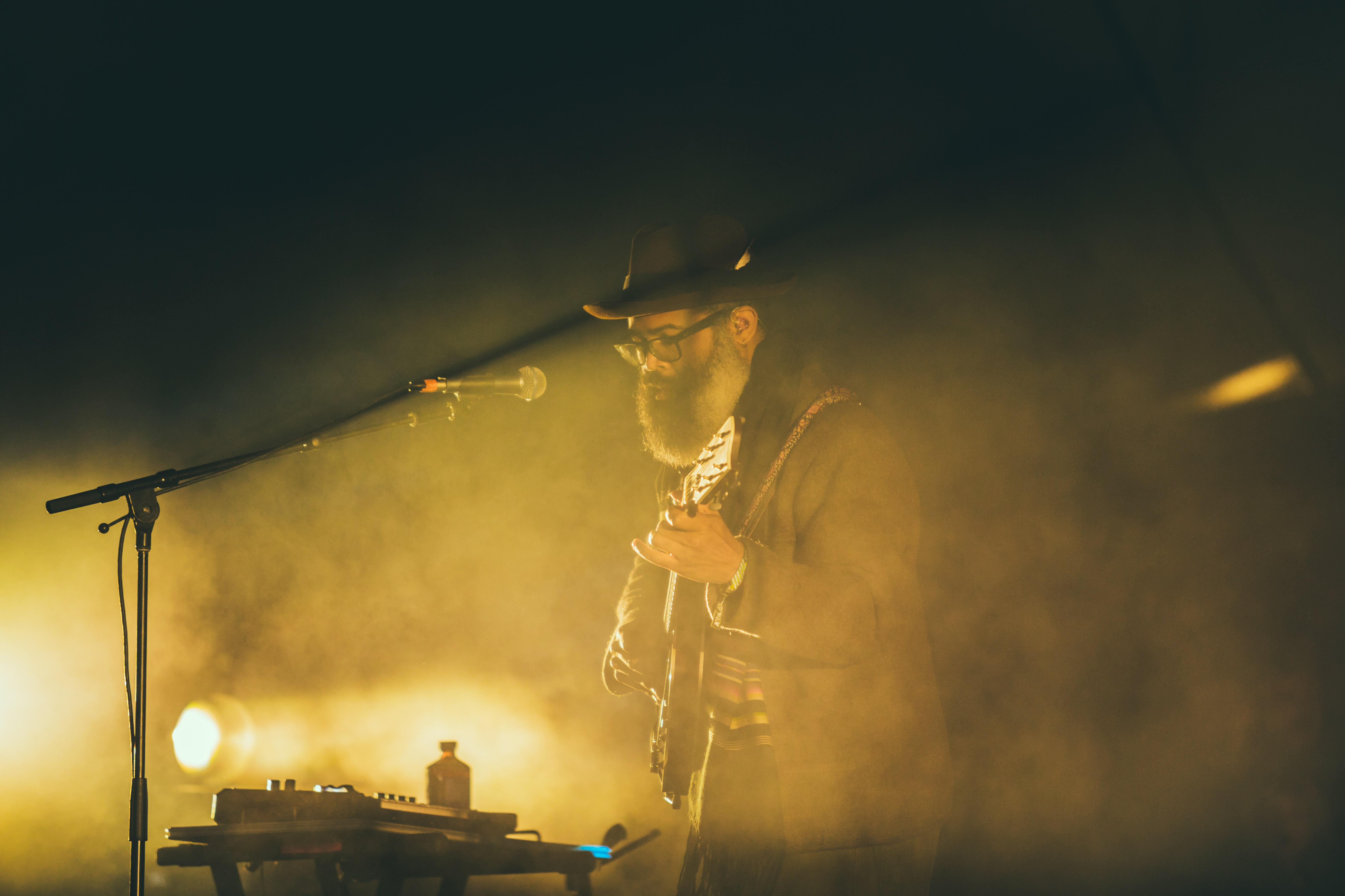 Musician glows in yellow smoke and light on stage at a show