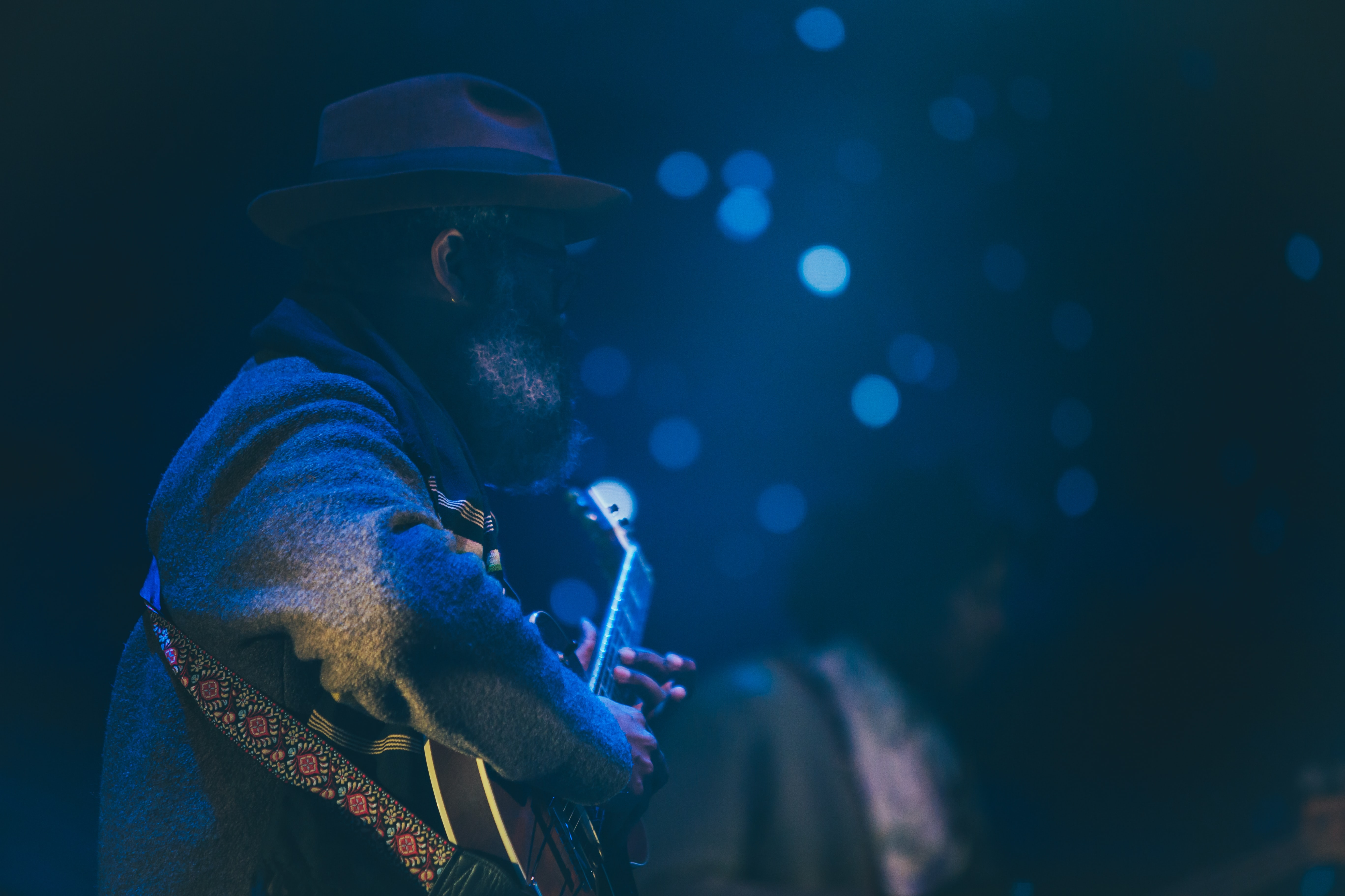 A bearded man in a hat playing the guitar with bokeh effect in the background