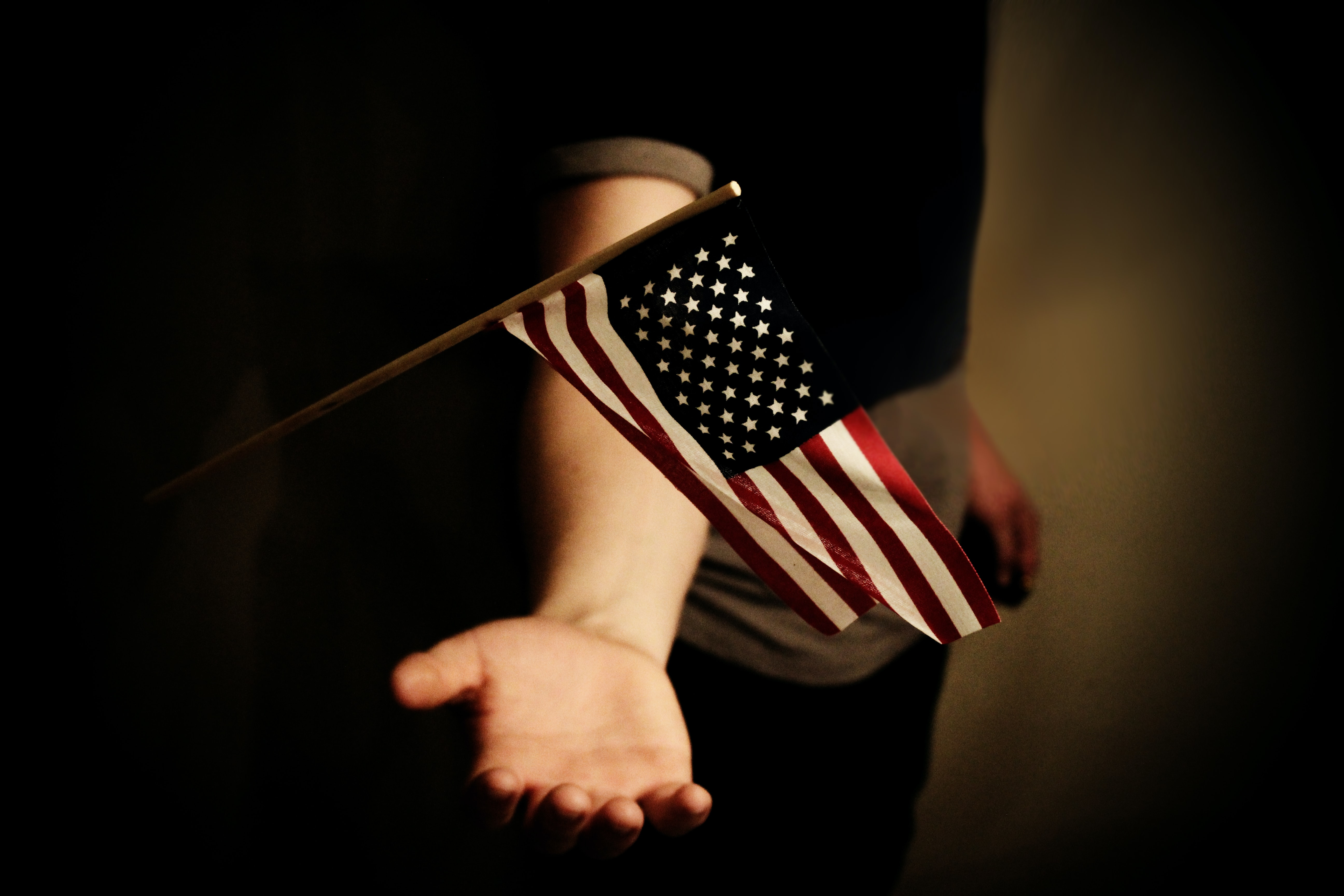 person with open palms below USA flaglet