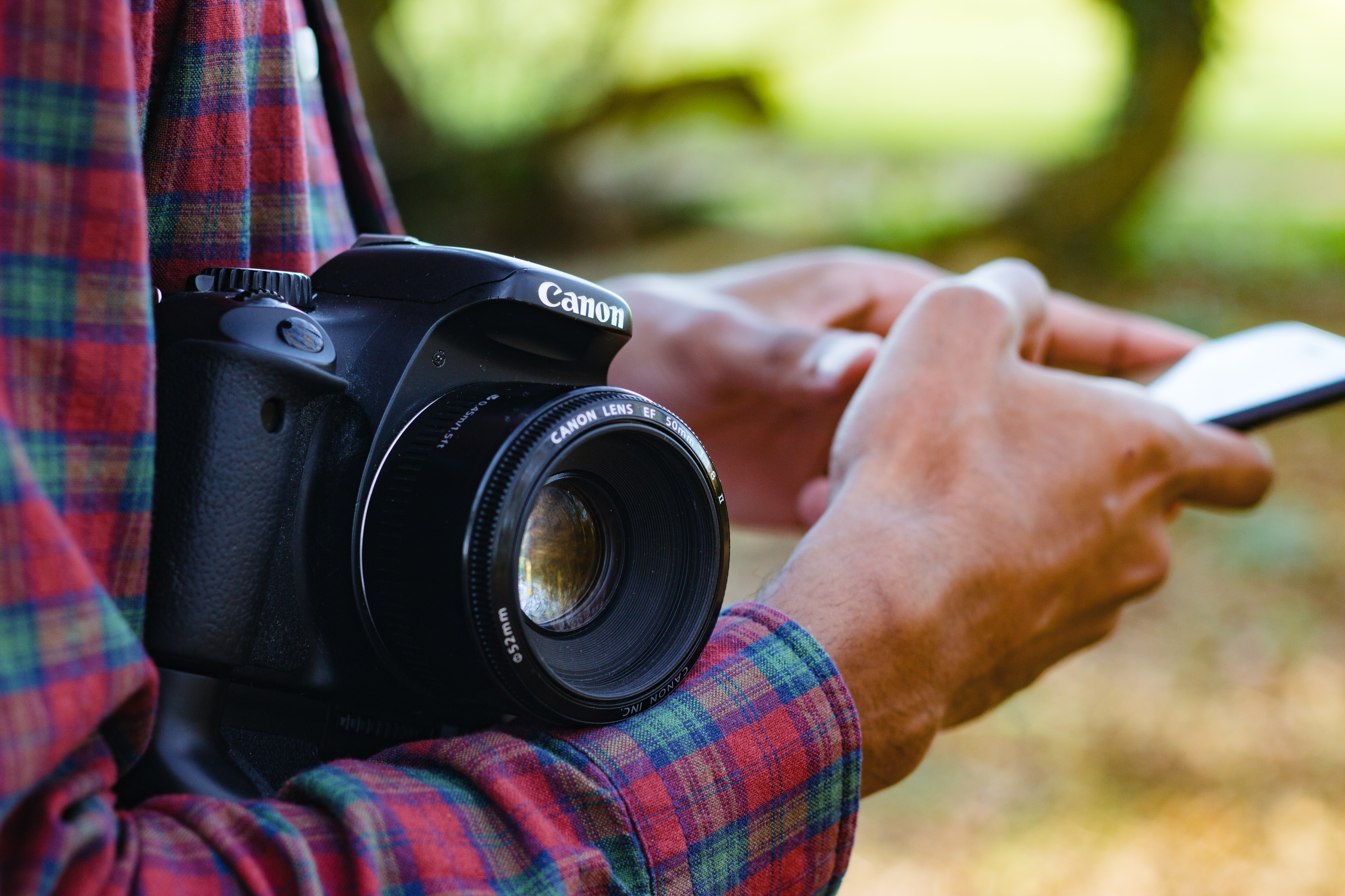 person holding smartphone with black Canon bridge camera on wrist at daytime