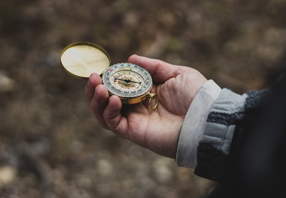 person using white and gold compass