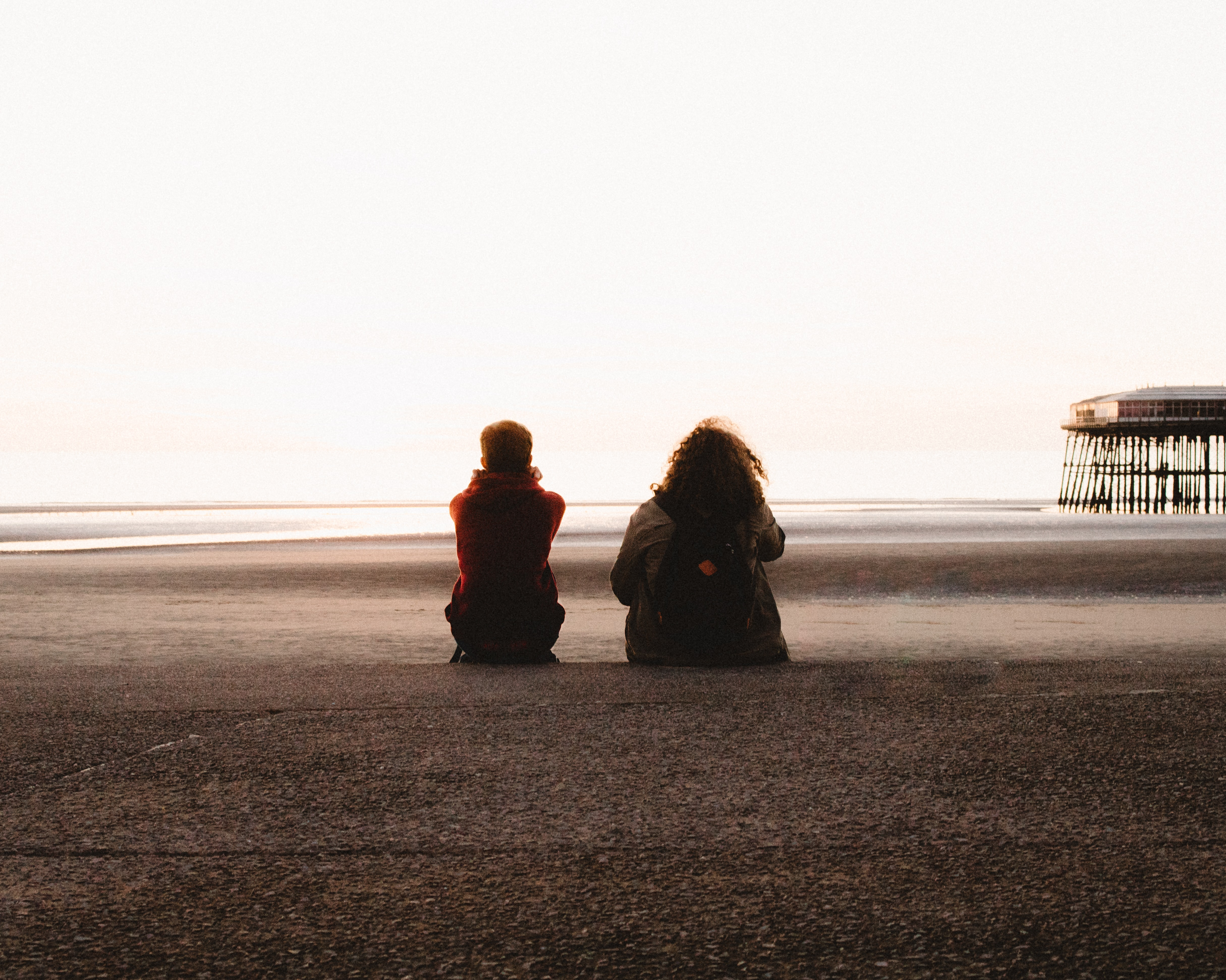two people sitting and looking at the sea
