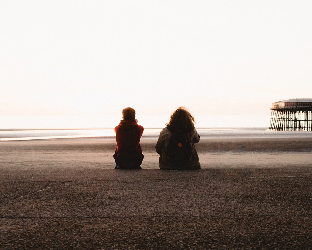 Two people sitting on the sands of Blackpool beach with a pier visible in the distance