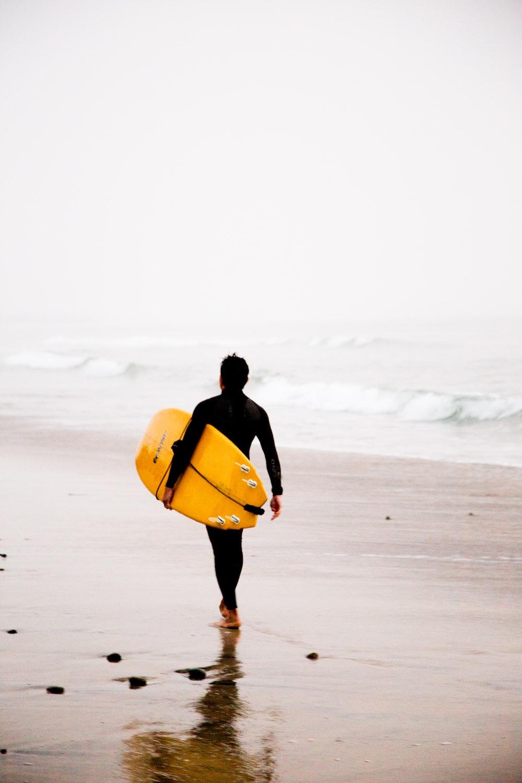 man holding yellow surfboard while walking on seashore during daytime