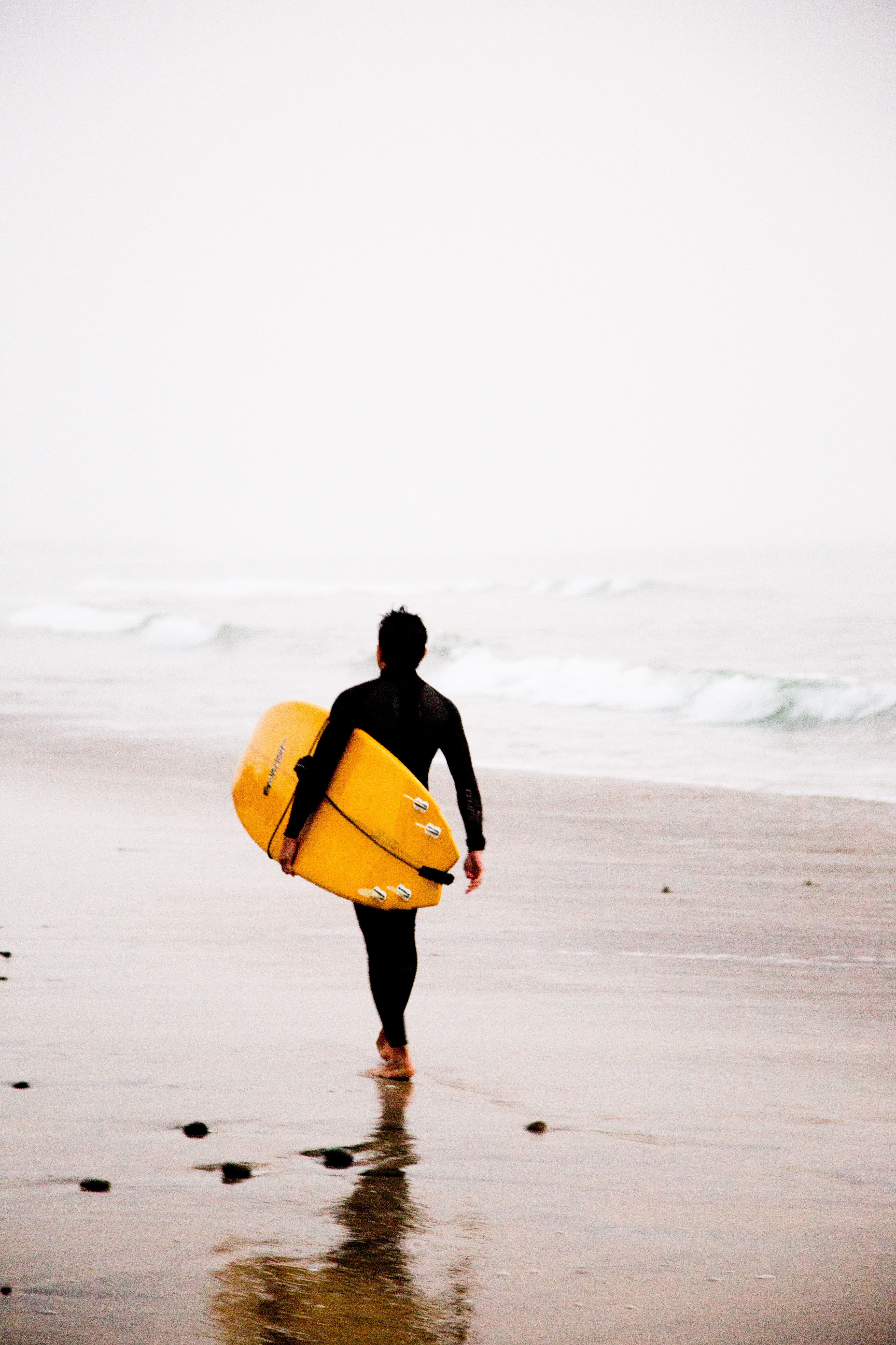 man holding yellow surfboard while walking on seashore during daytime