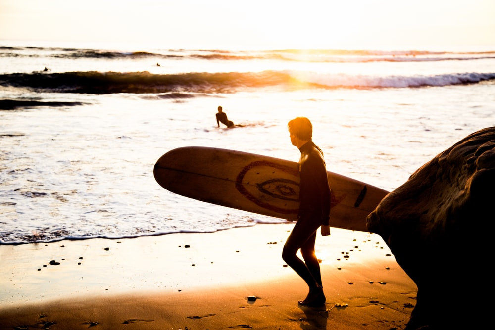 man carrying his surfing board at the seashore