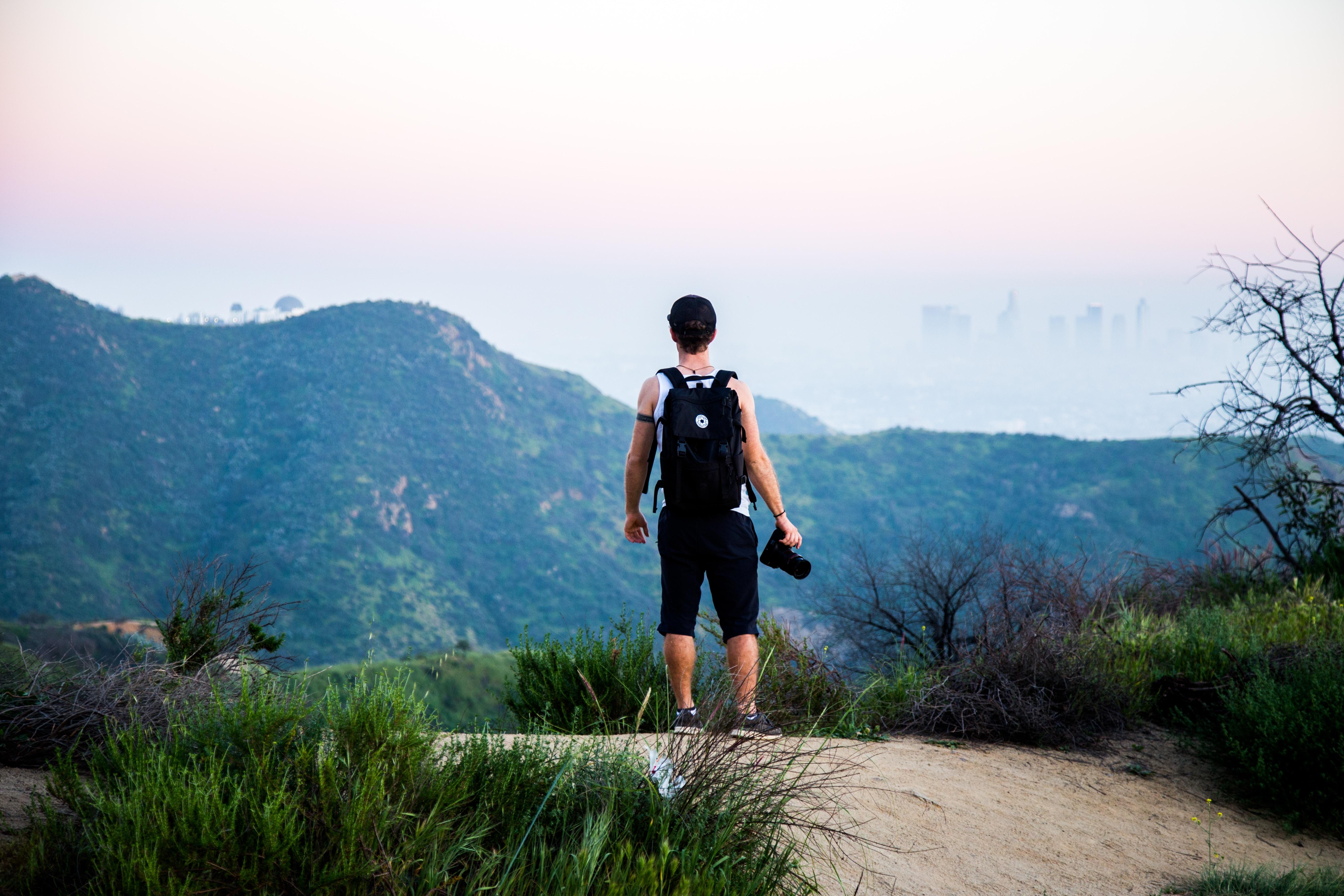 man wearing black backpack standing near mountain at daytime
