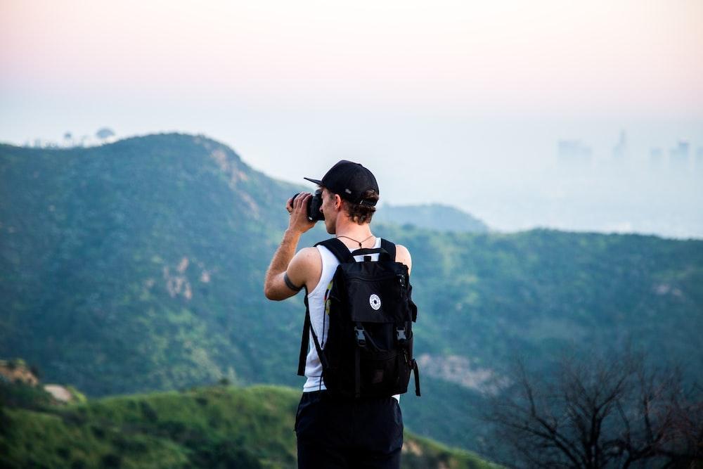 man wearing black backpack using telescope