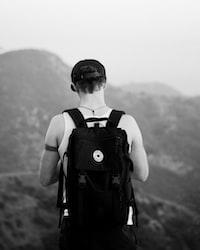 man standing facing mountains wearing backpack