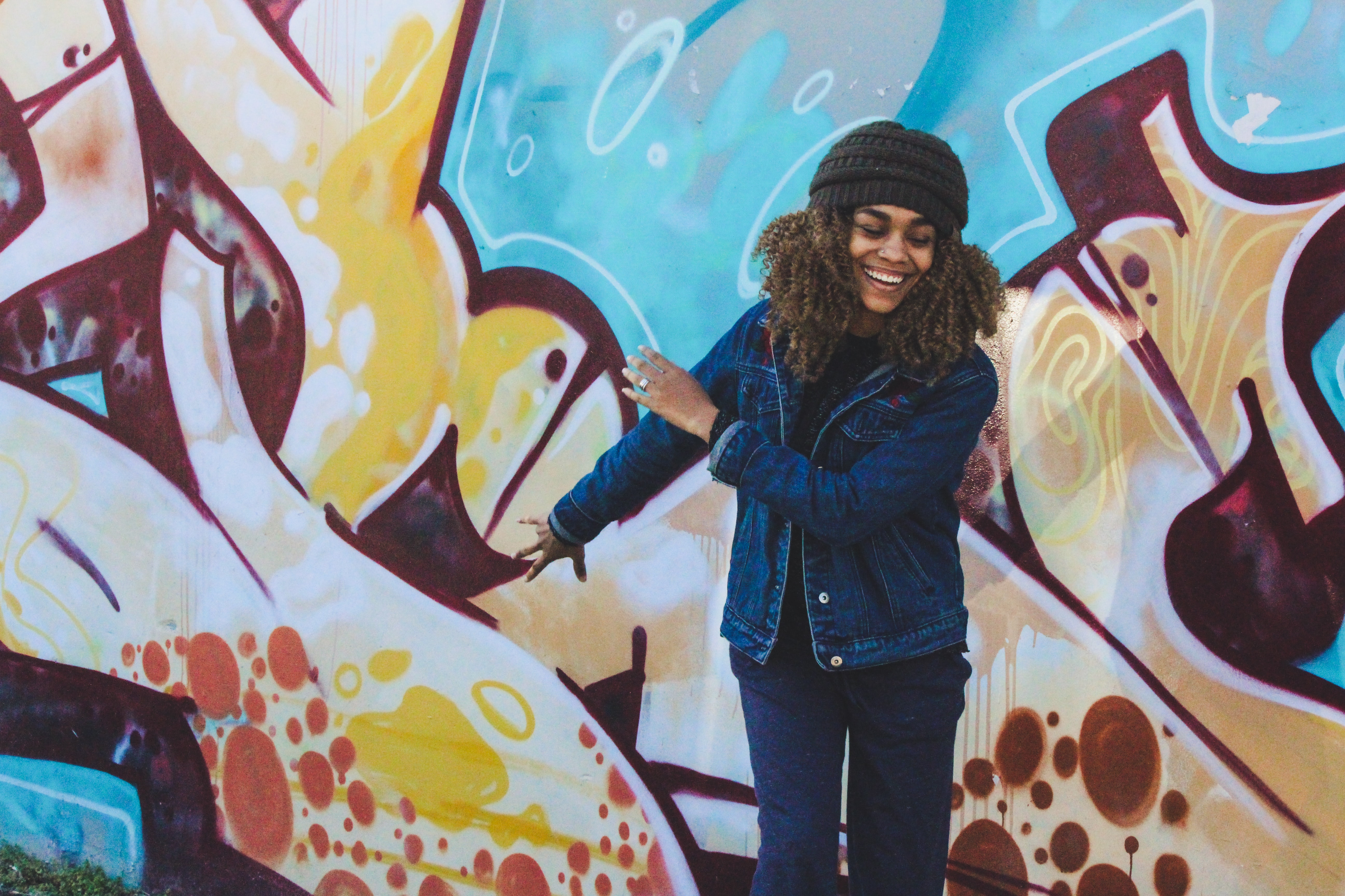 Young woman wearing denim jacket and beanie smiling in front of bright graffiti wall