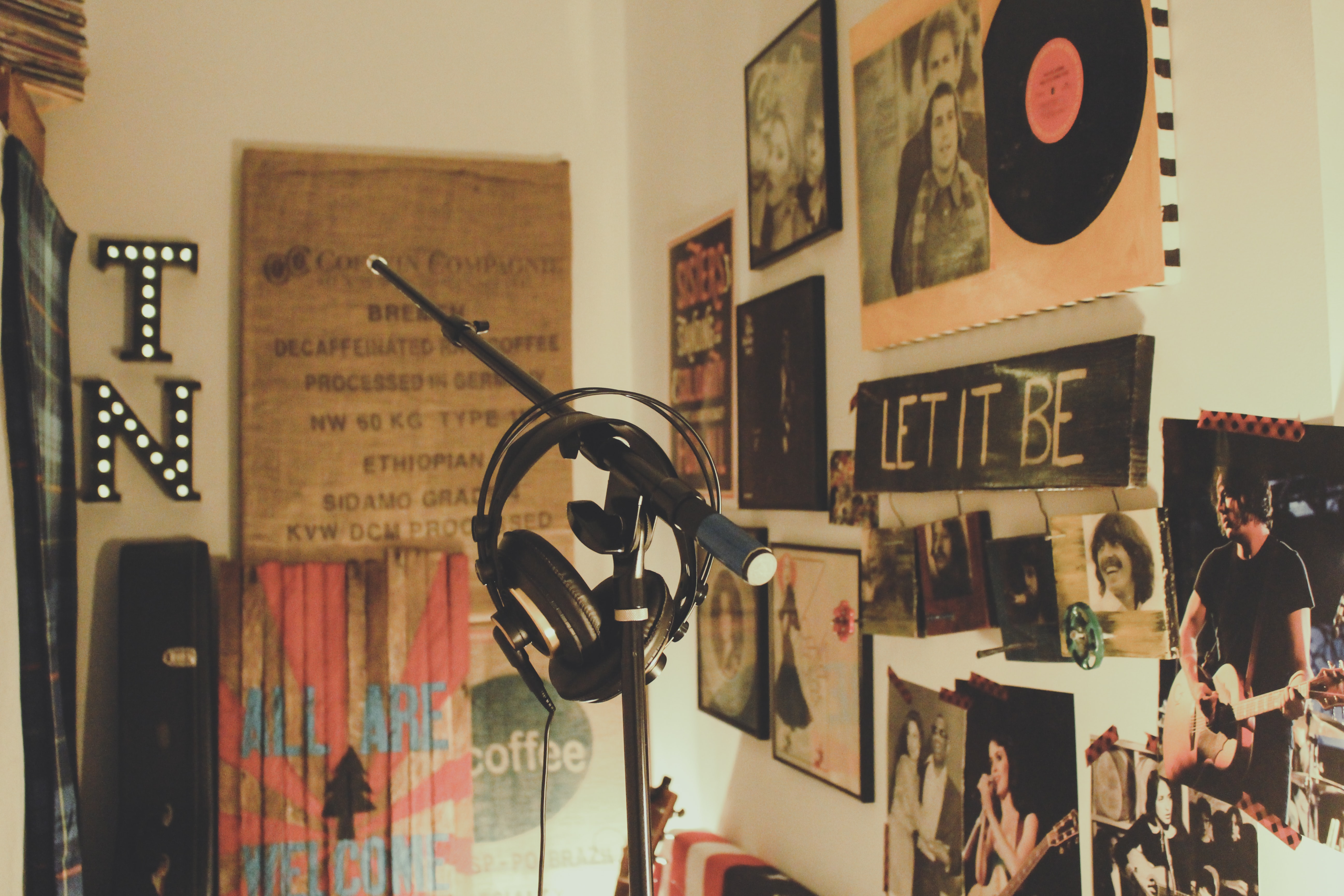 Headphones hanging from a microphone stand in a room with falls covered with music posters