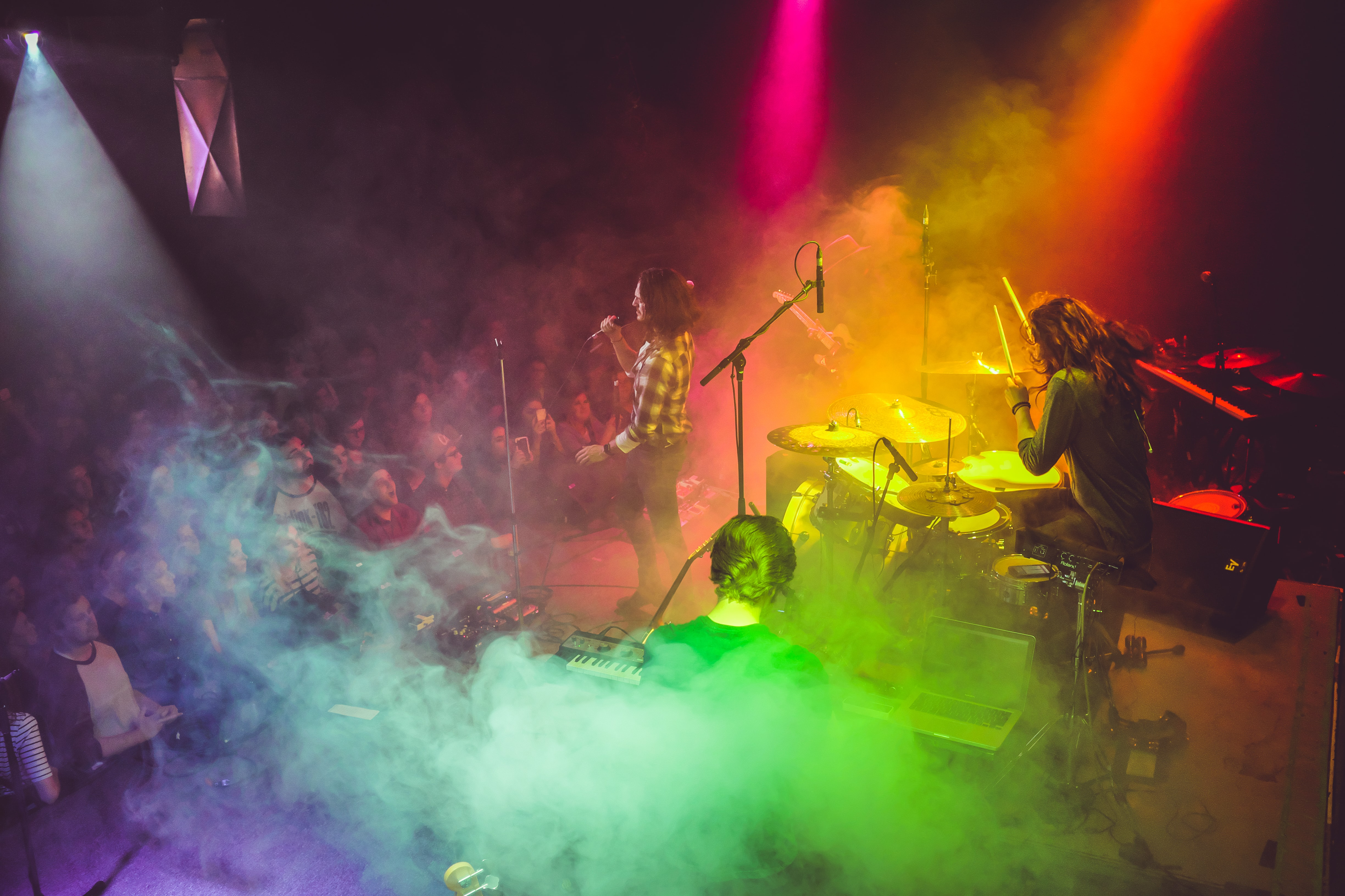 A band performing on stage with rainbow-colored lights flooding them from above