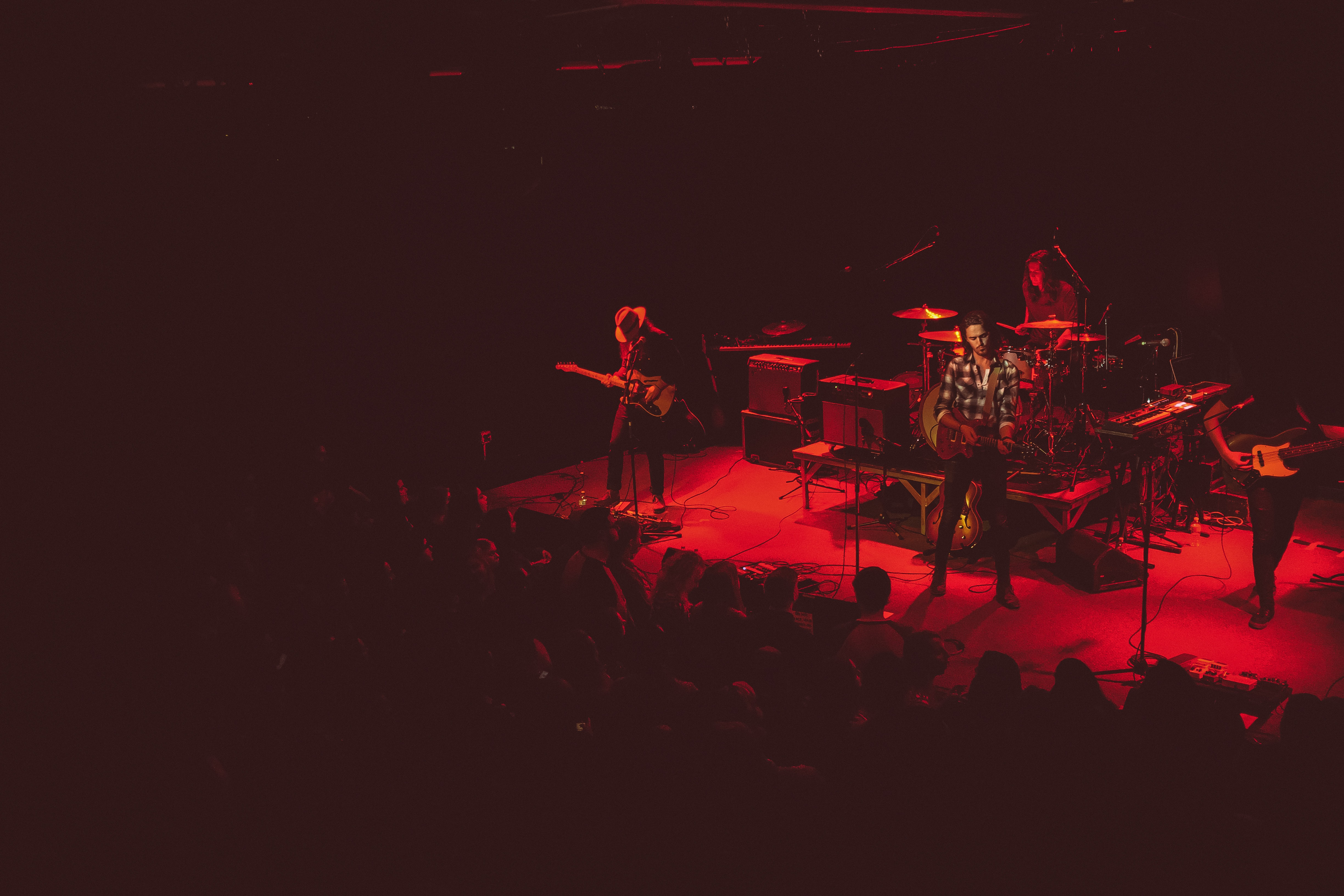 A band performing on stage under red light in Metro Music Hall