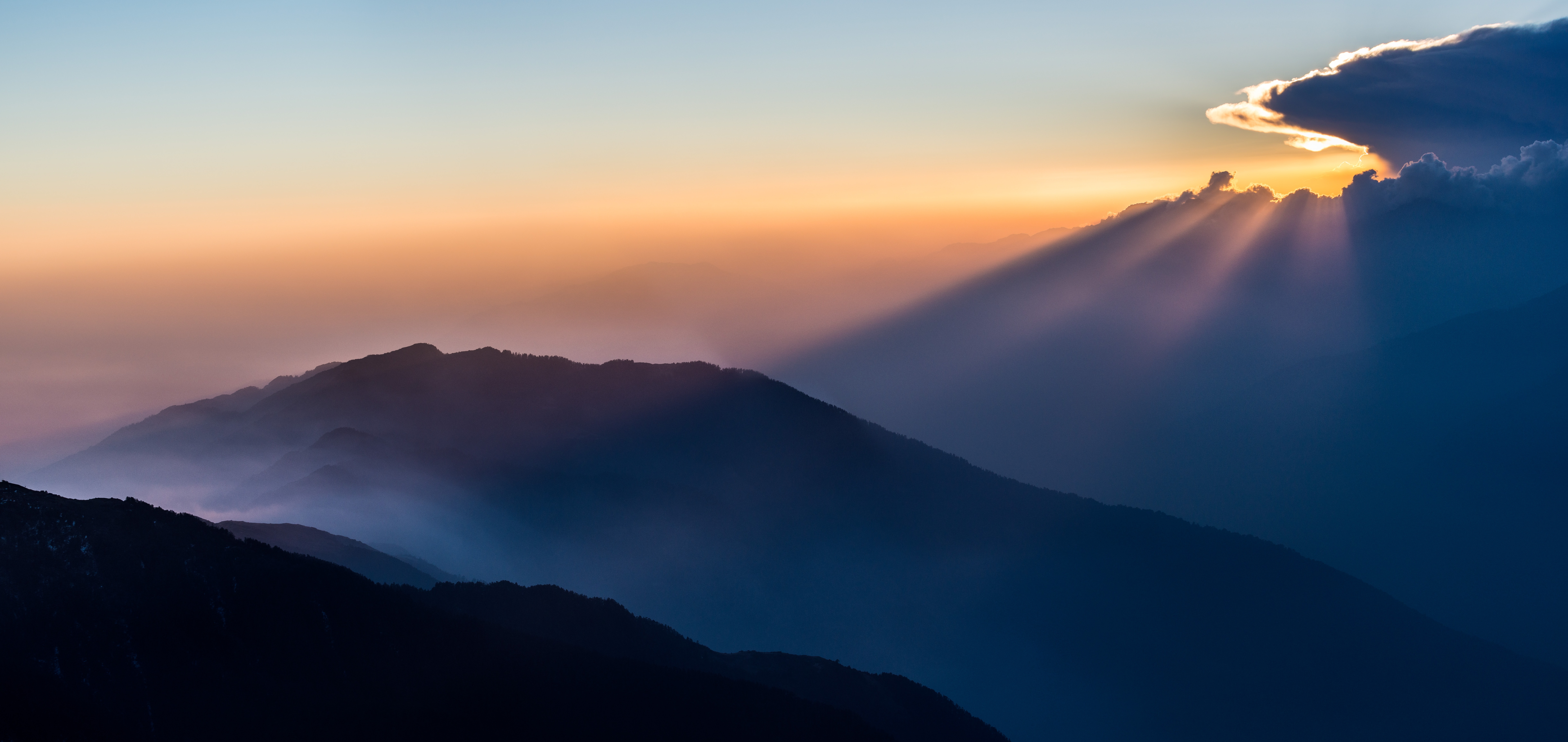 Mountain ridges silhouetted against the blue and orange sky during sunset