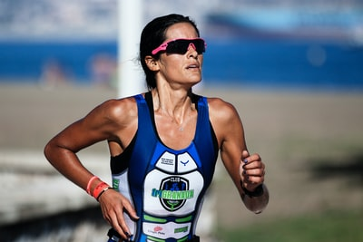 selective focus photography of woman running athlete teams background