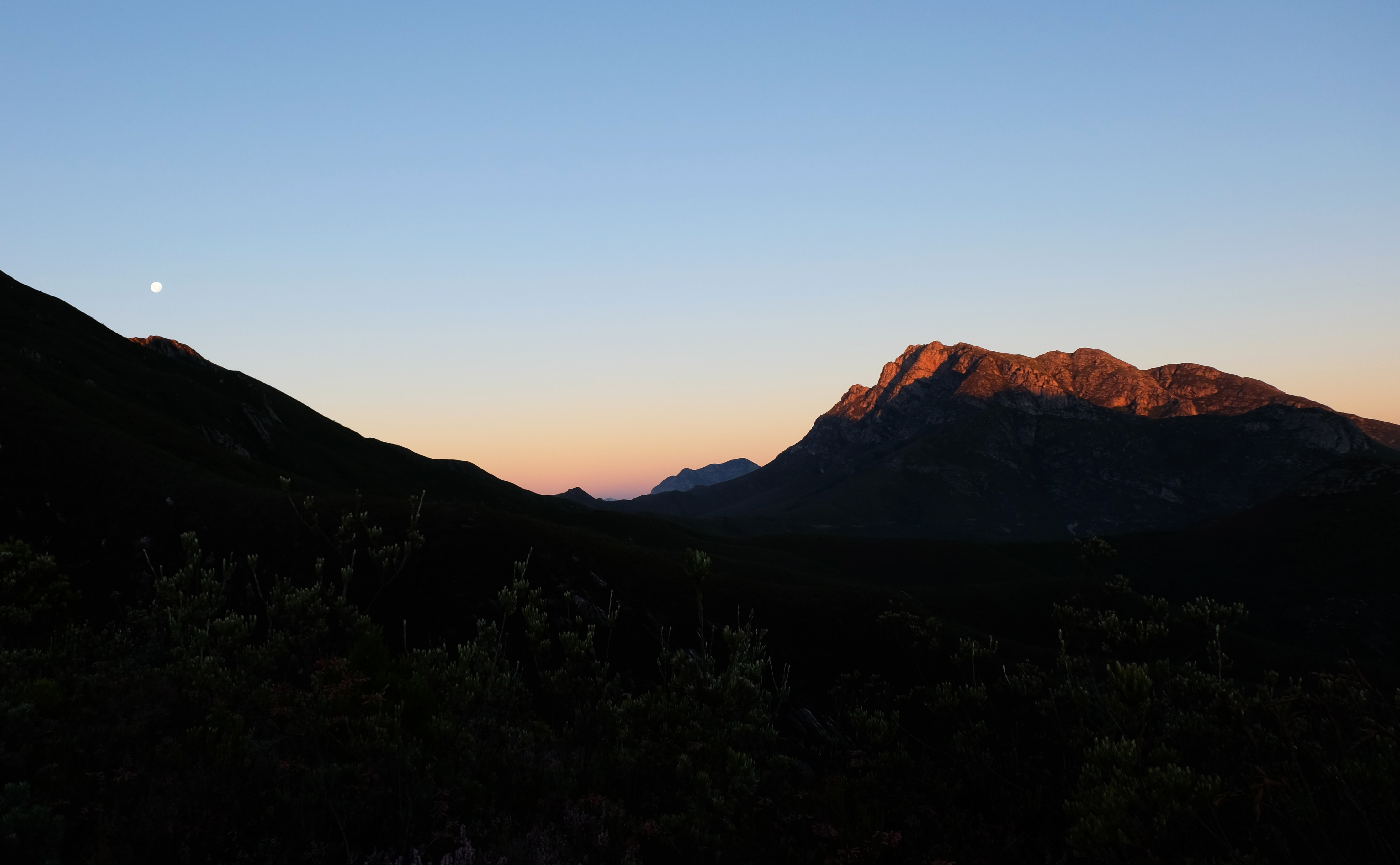 A full moon in the evening sky over the silhouettes of jagged mountains in Outeniqua Pass