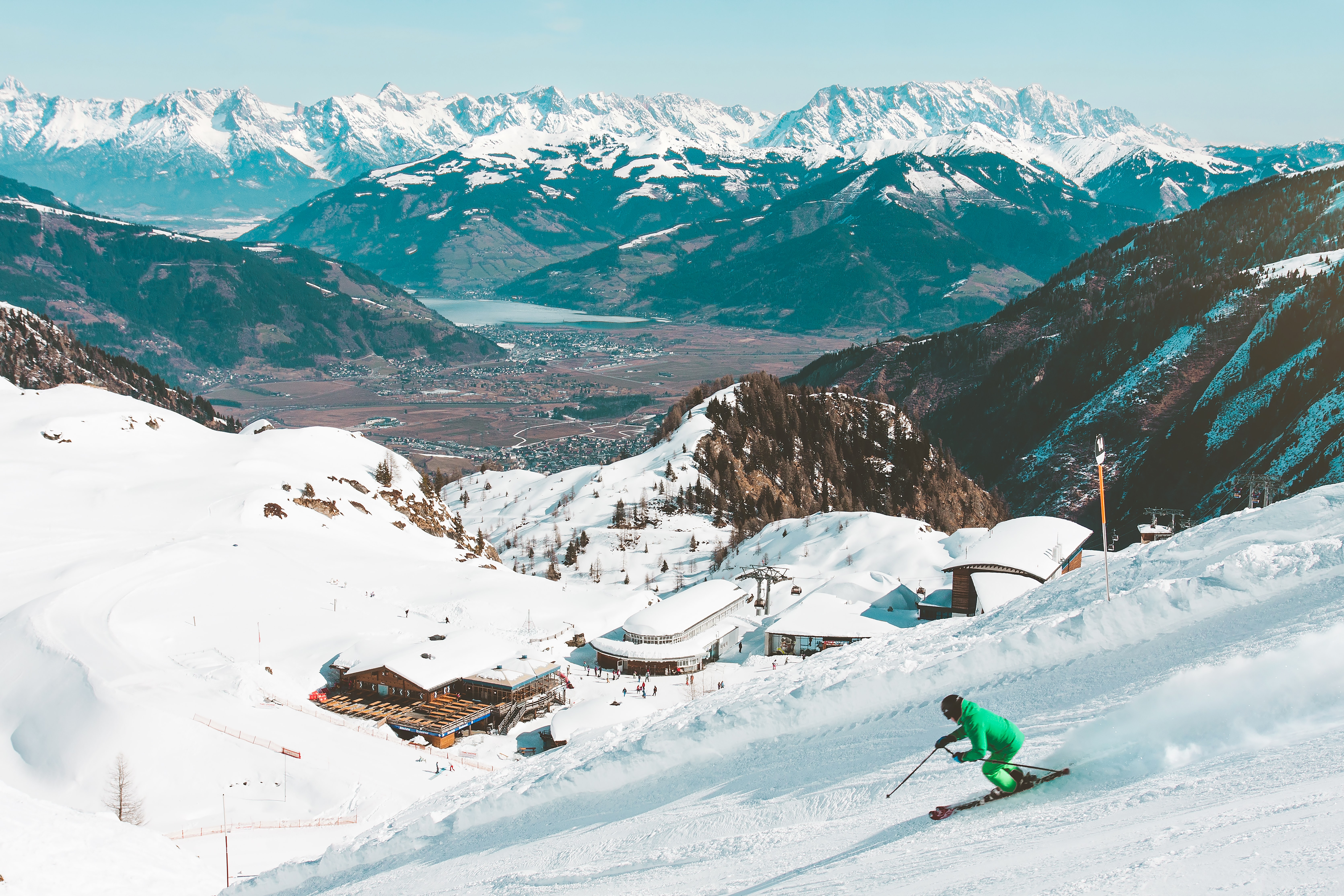 person riding on skis during winter surrounded by mountains