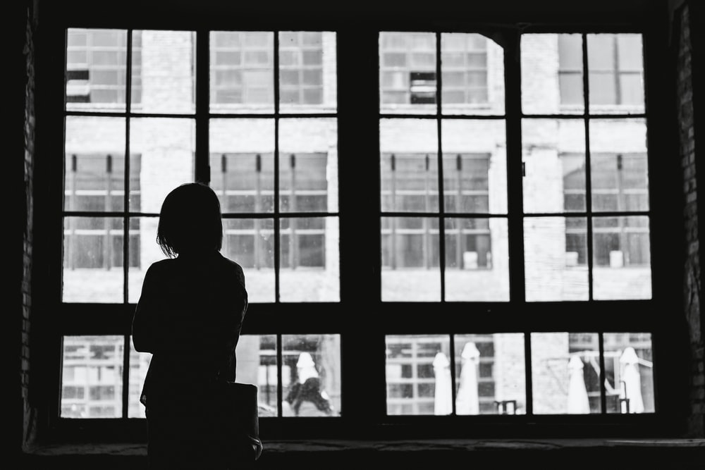 grayscale photography of woman facing window