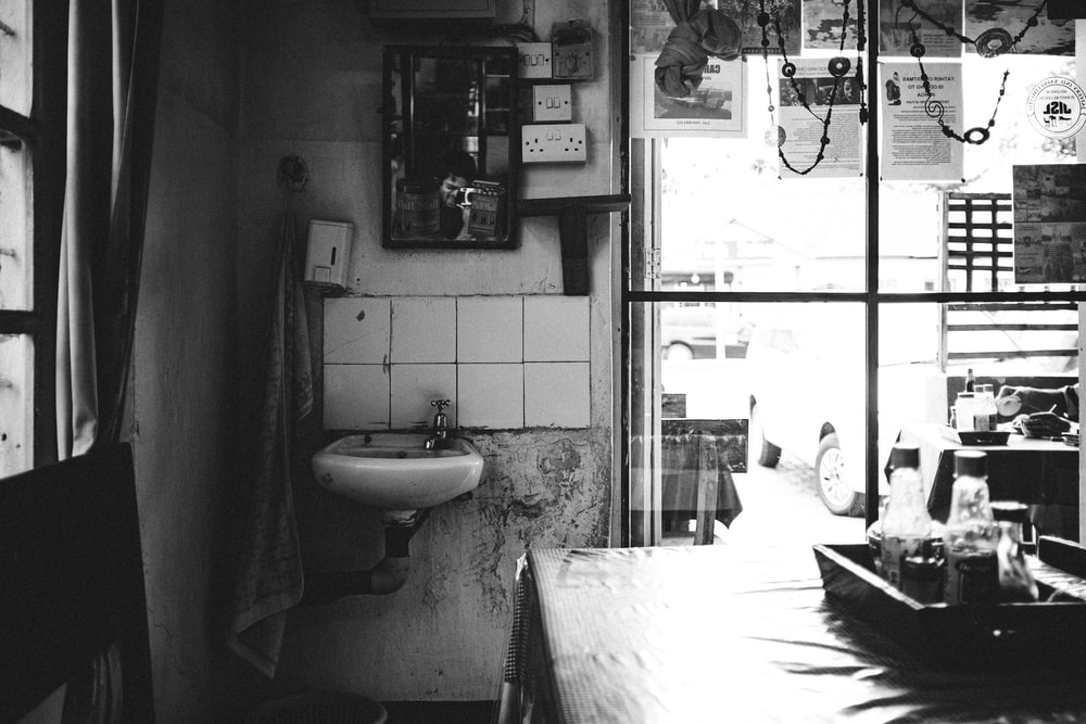 grayscale photo of woman in white dress standing near sink