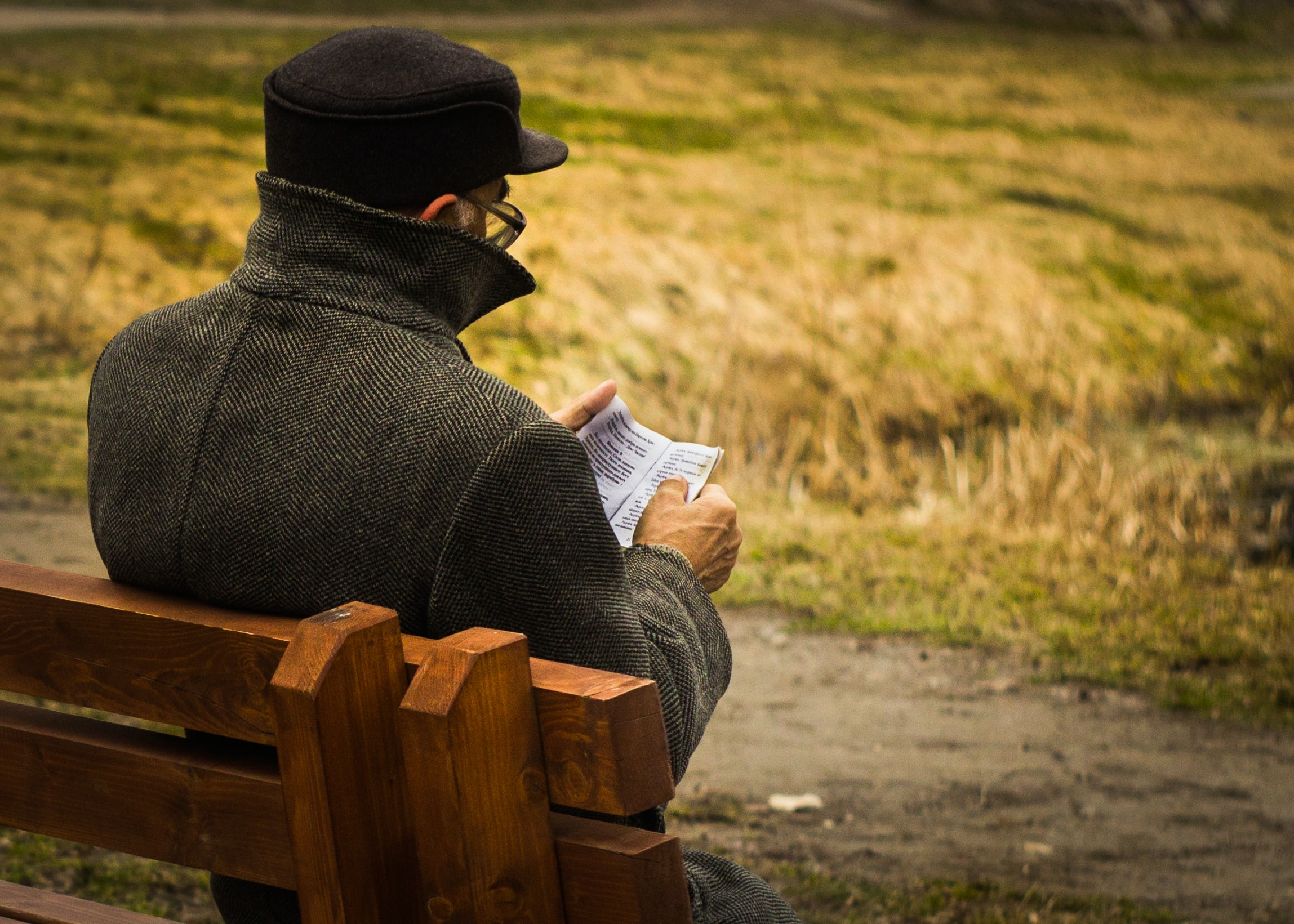 man holding paper sitting on bench