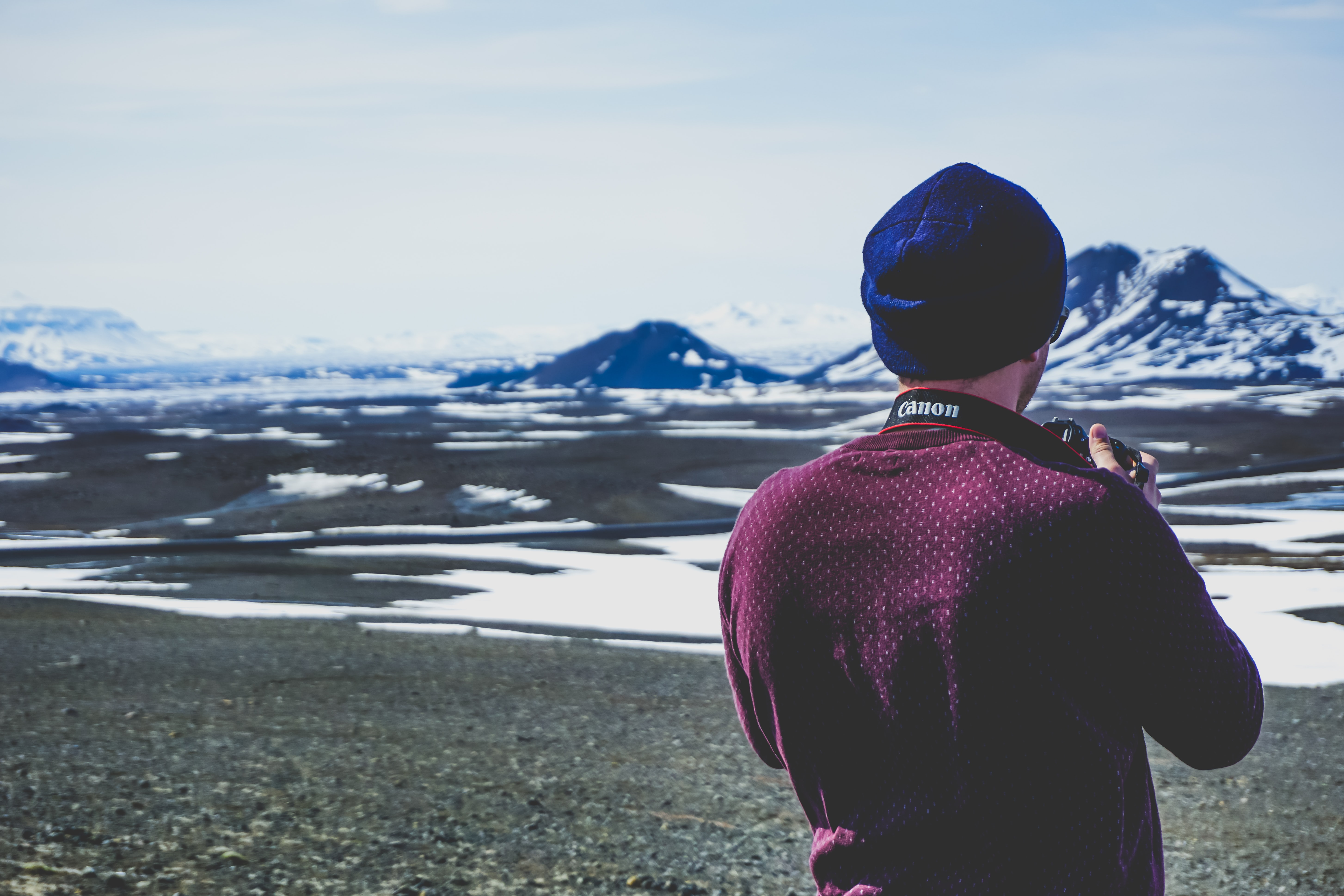 A male photographer snaps a photo of the mountains in Iceland on his Canon camera