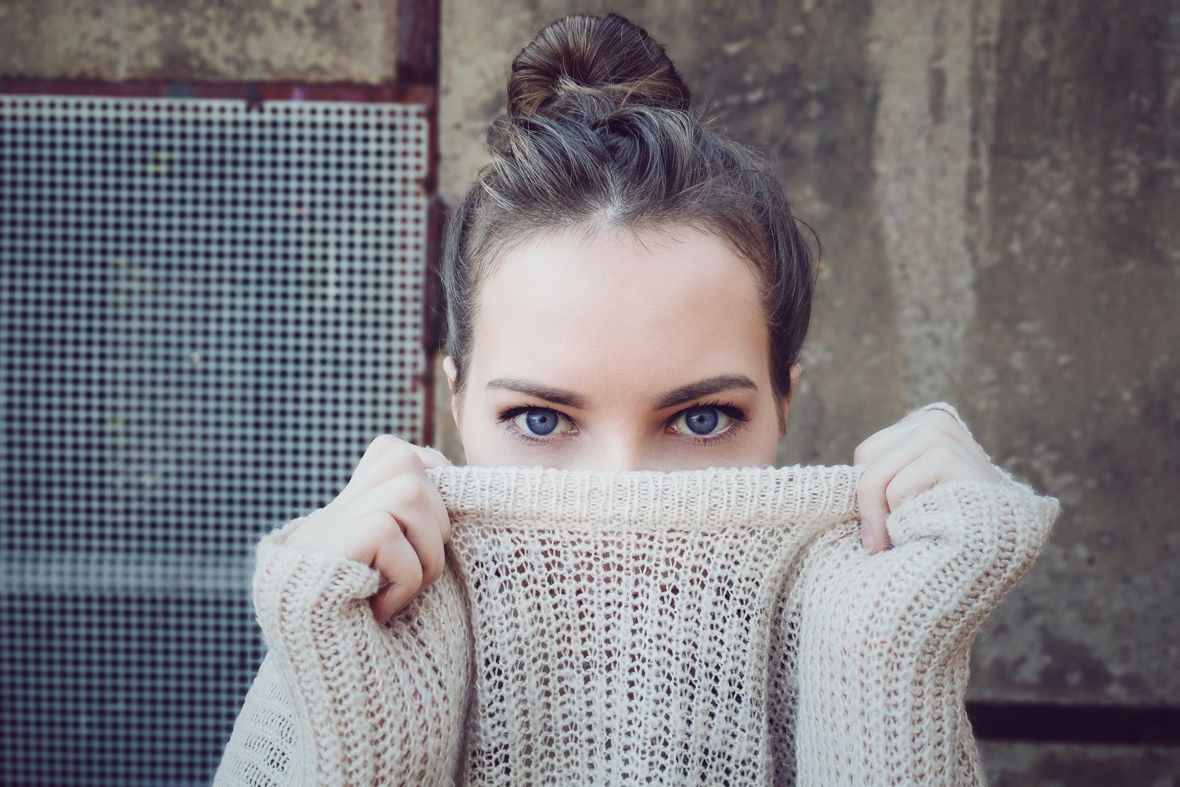 A brunette woman with blue eyes holding her knit sweater over her mouth in Essen, Nadrenia Północna-Westfalia, Niemcy