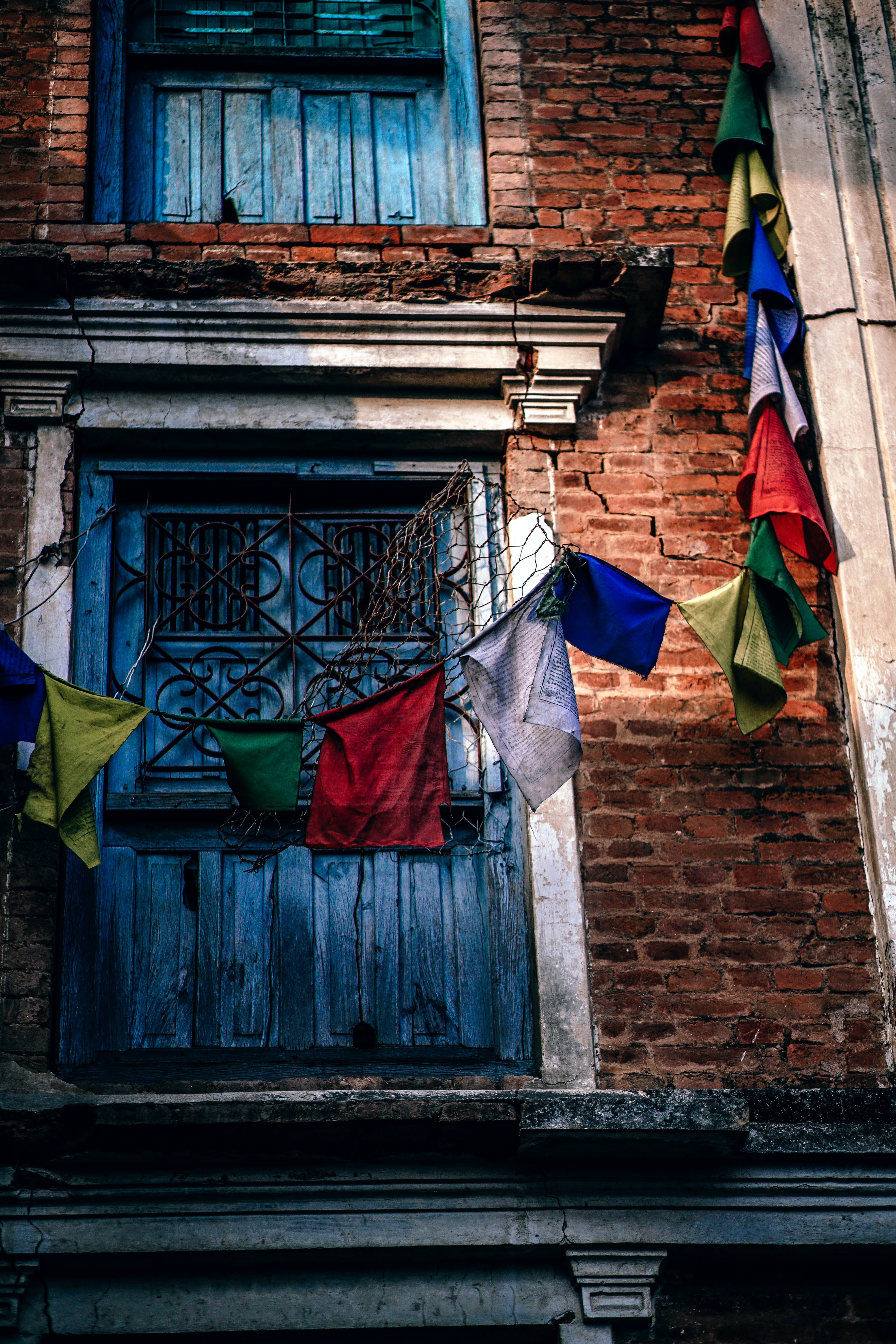 A brick building with blue window shutters and colored flags around it in Swayambhu Stupa