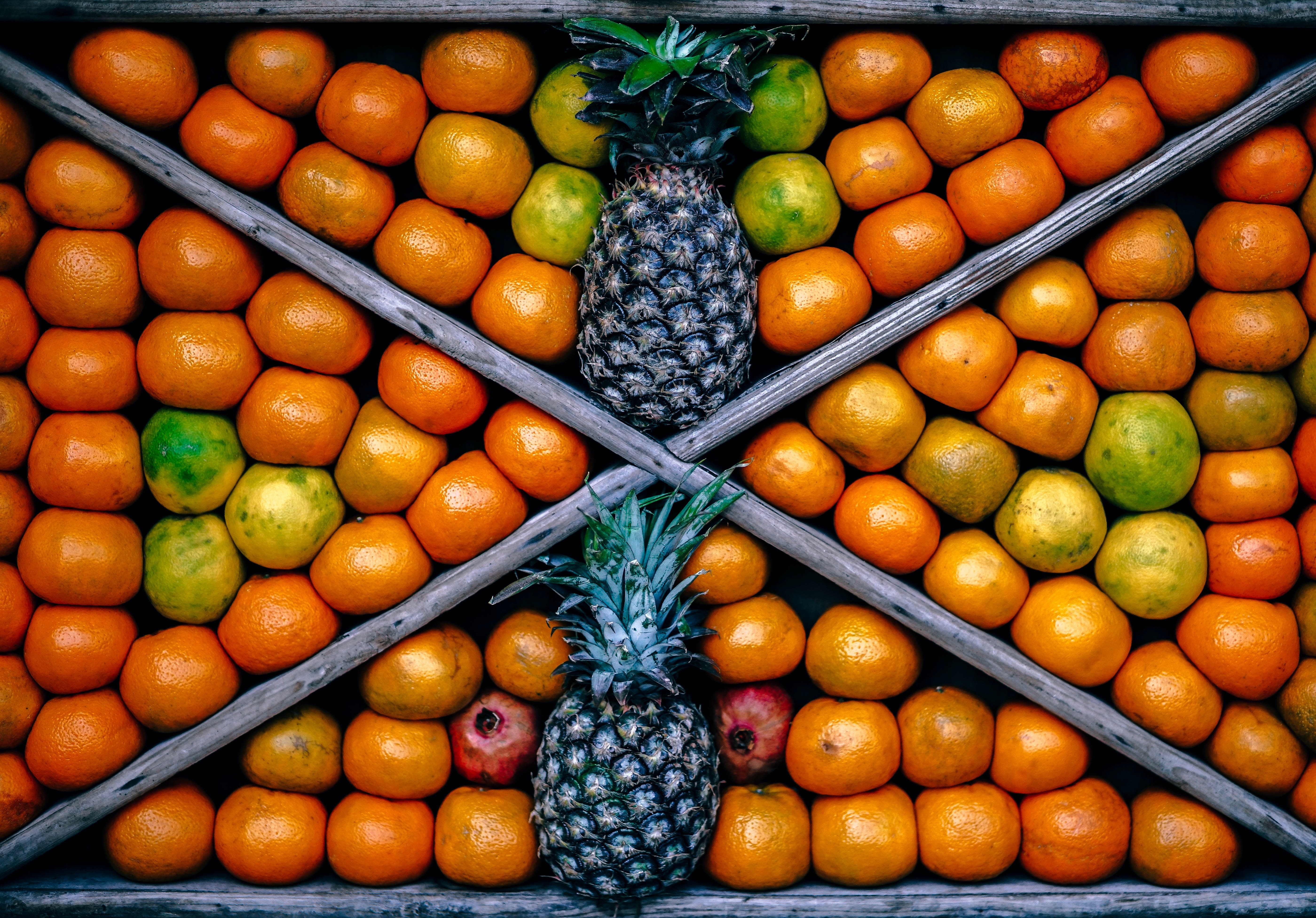 Top view of a fruit bin featuring pineapples and other fruits.