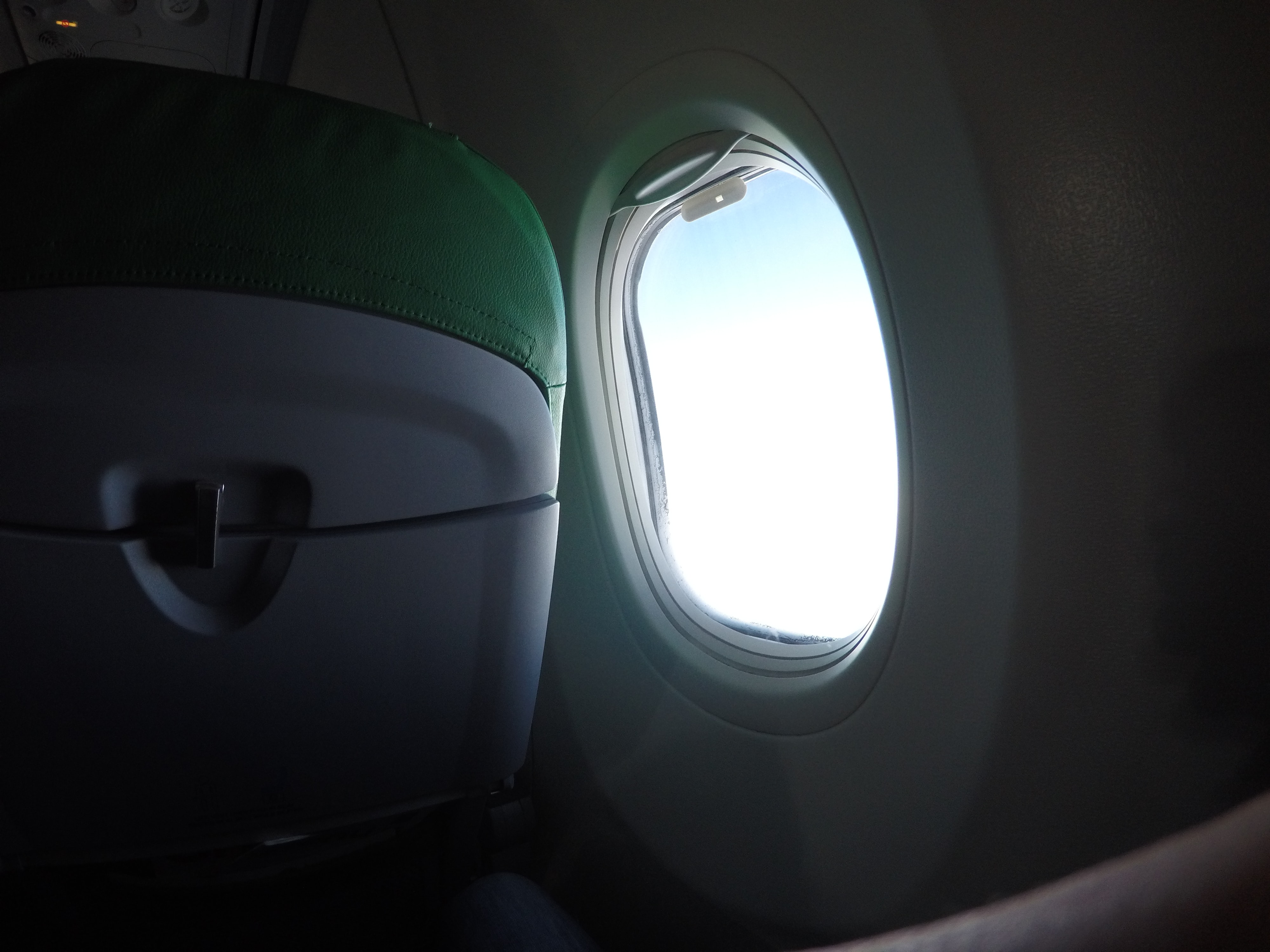 A round airplane window with pale light shining through it