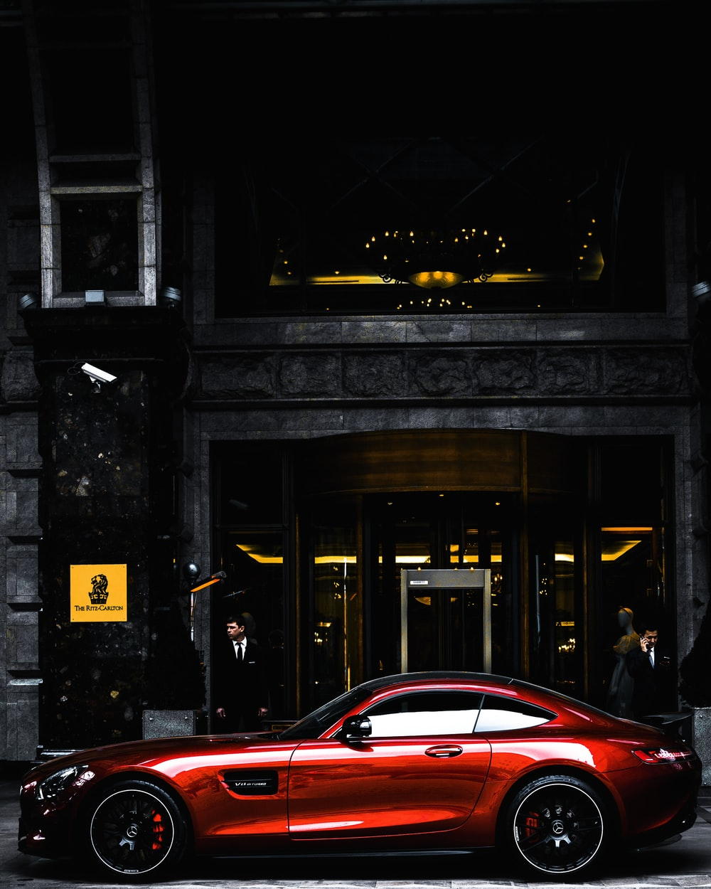 red coupe parked in front of black and gray building during daytime