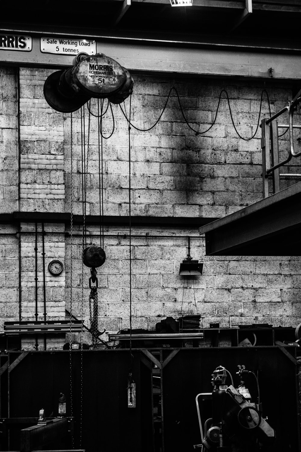 grayscale photography of wall with ropes and machine