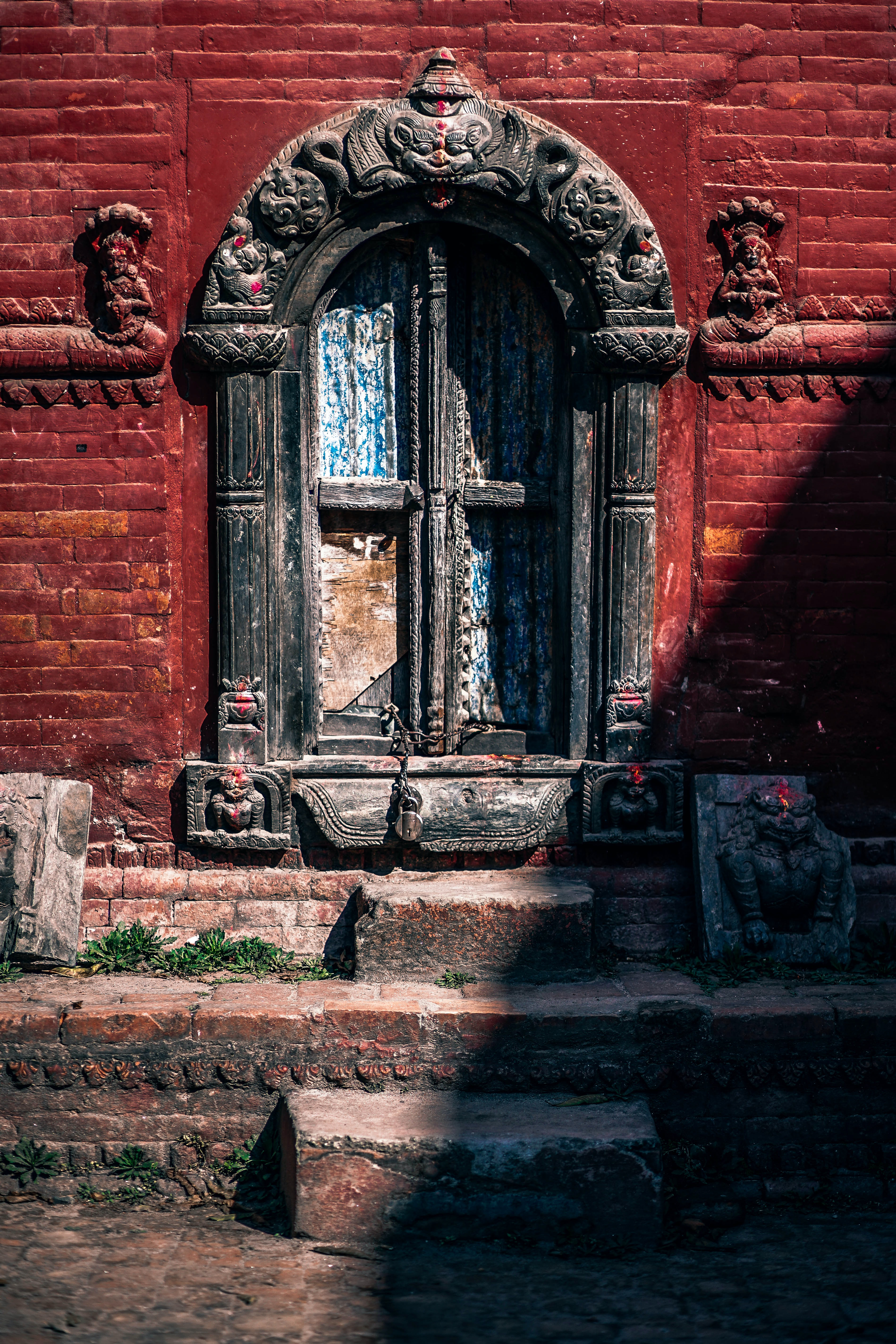 A old window surrounded by an ornate stone carving in Kathmandu