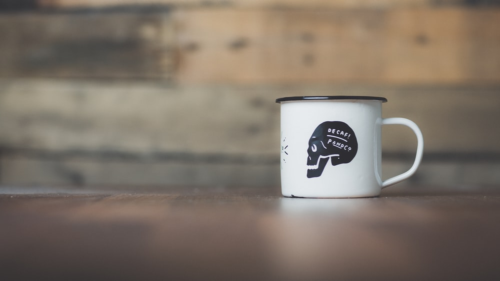 white ceramic mug on brown wooden table near gray wall