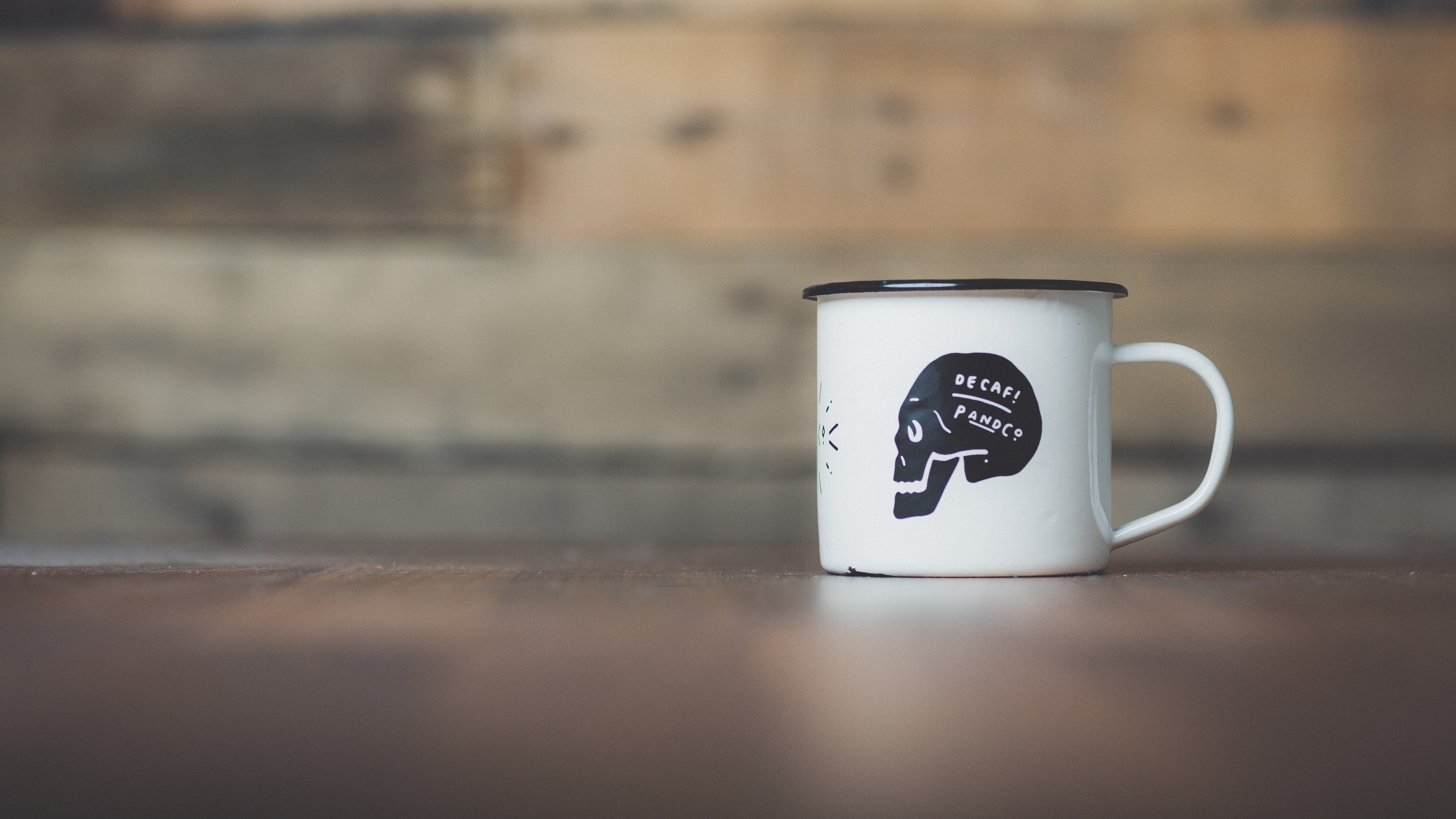 Tin white mug with black skull reading Decaf on it in front of wooden background