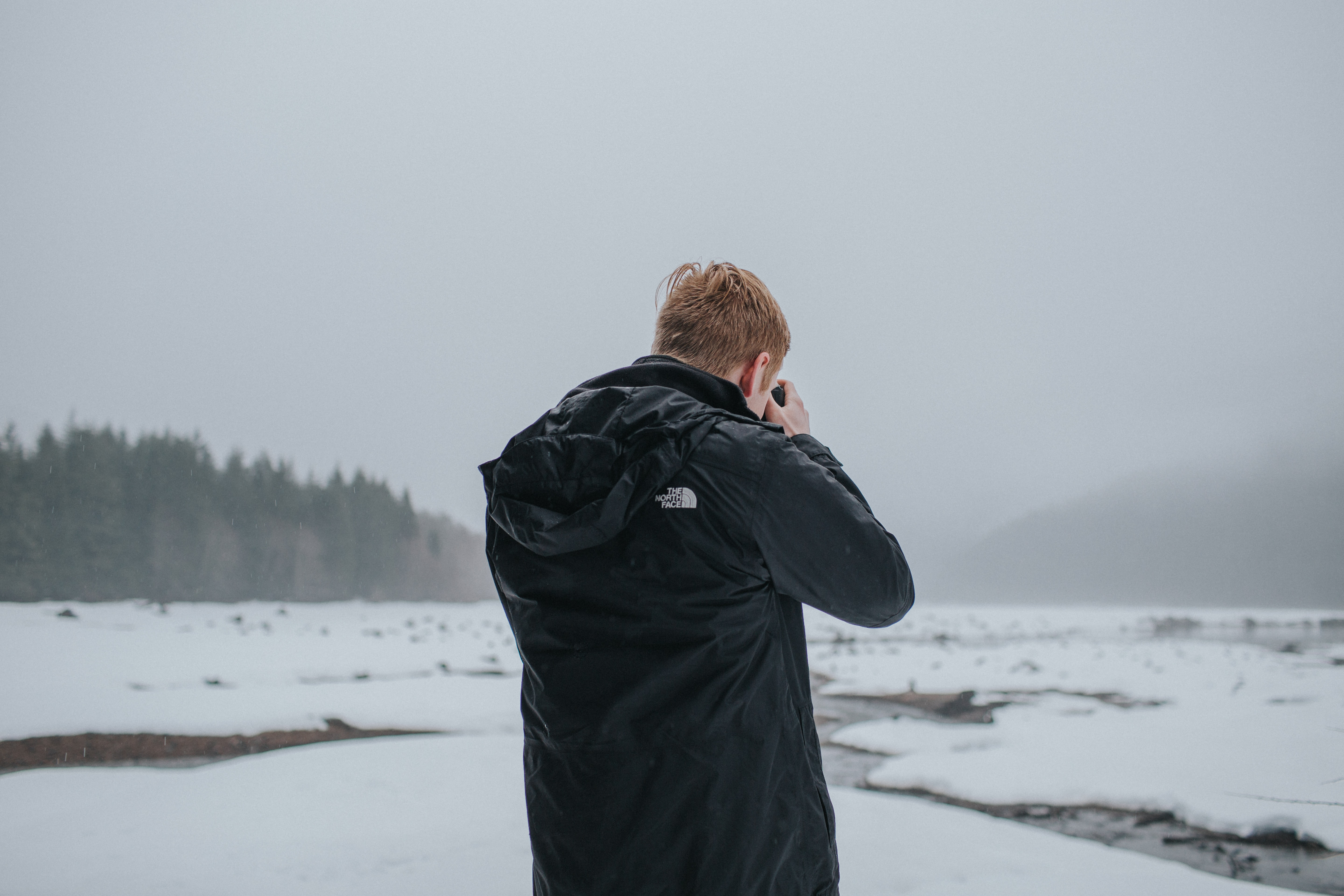 Man in a northface jacket taking a photo of the snow