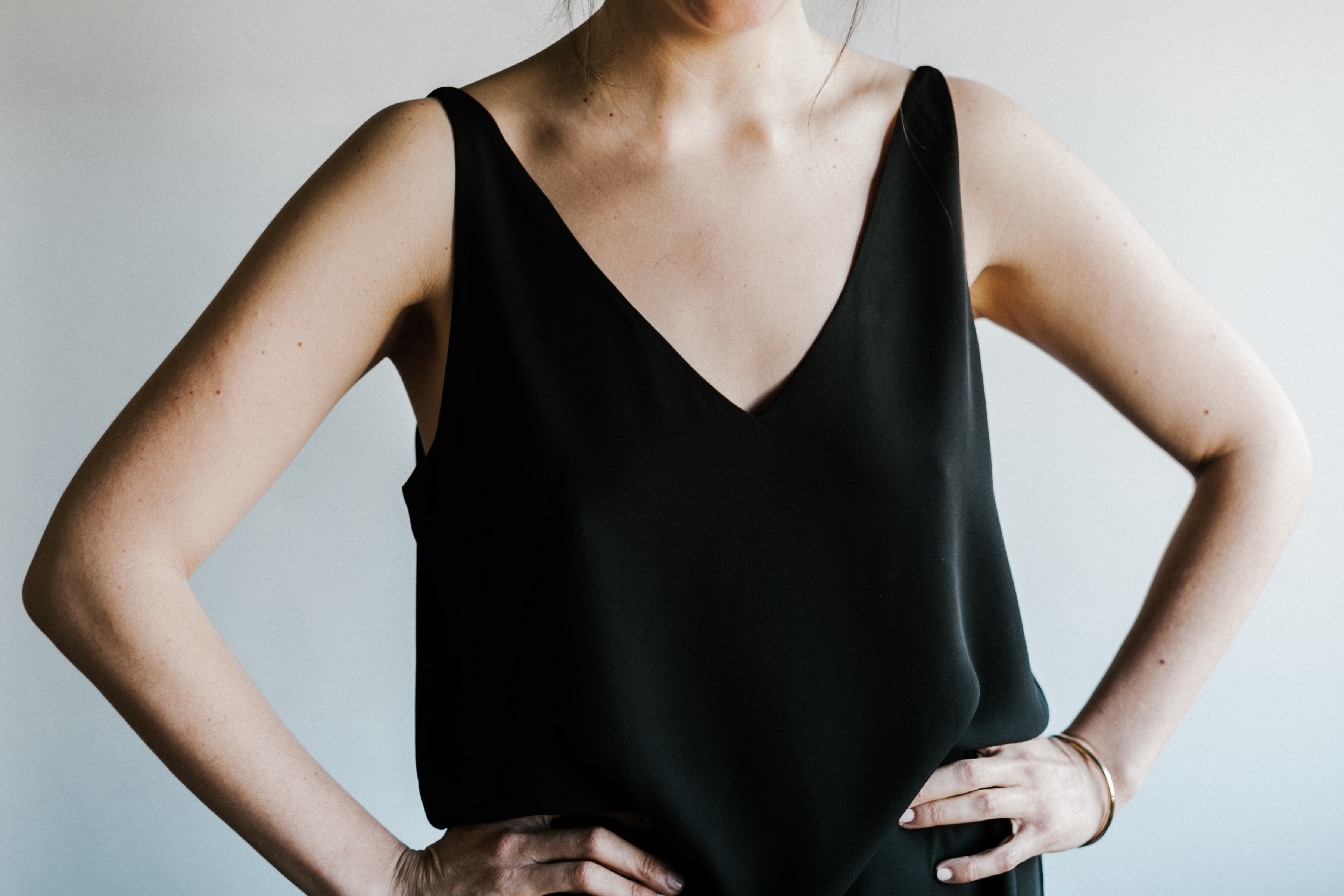 woman in black V-neck sleeveless top with hands on her waist