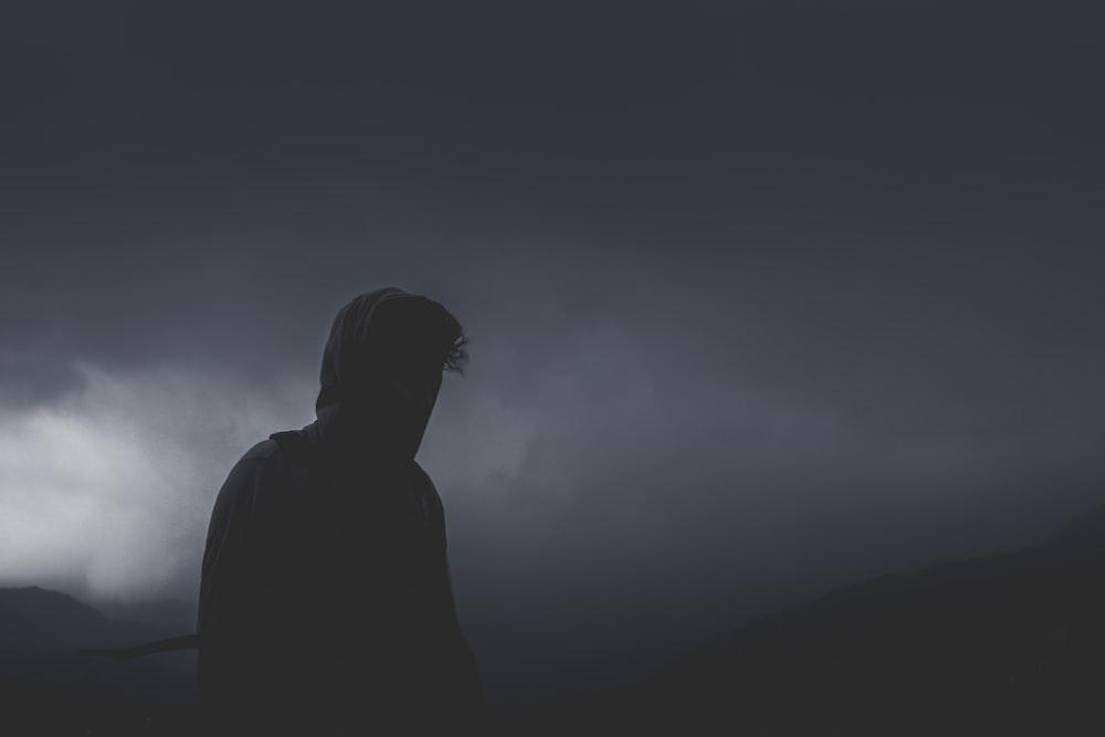 man looking forward on cloudy path