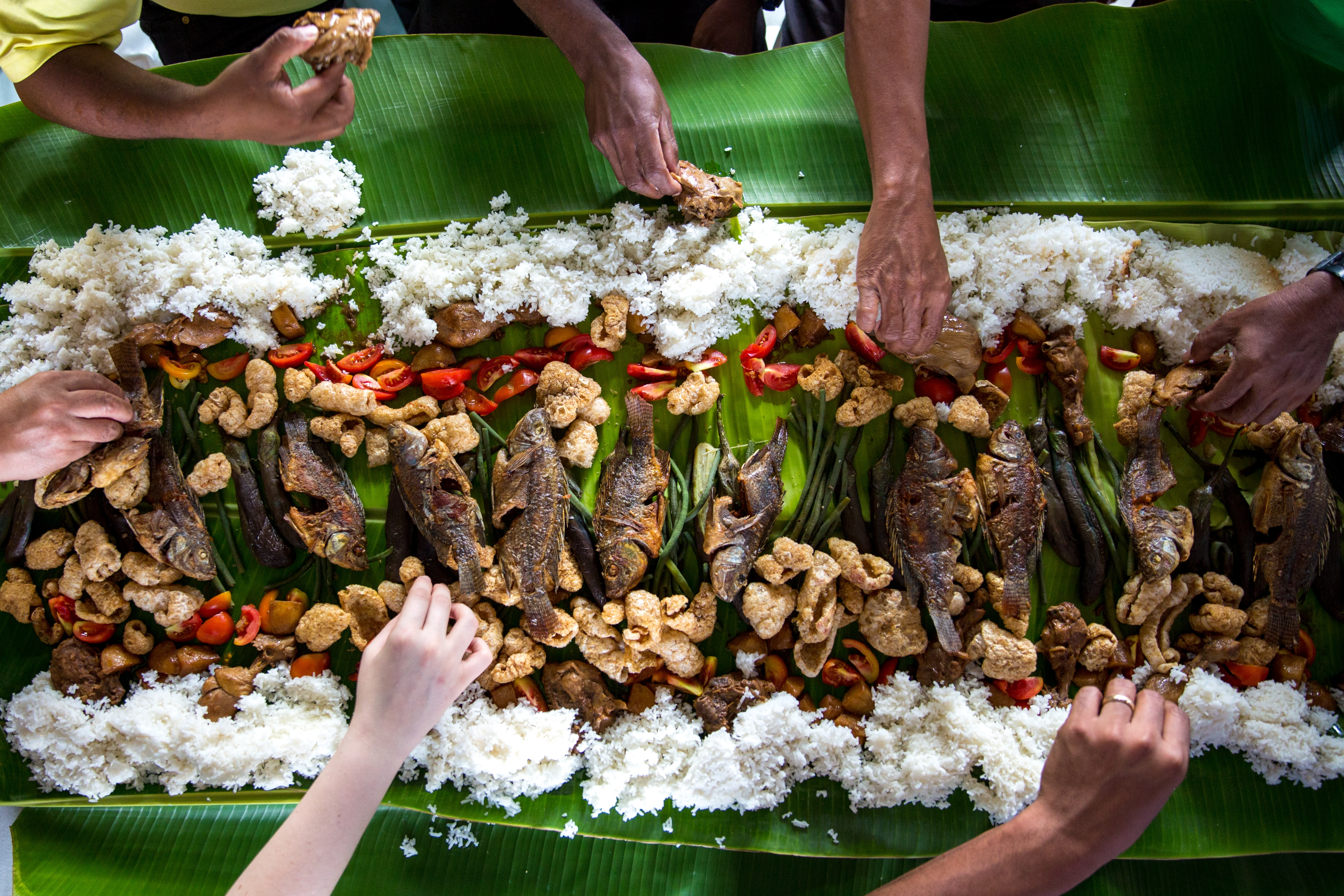 Several people eating fish, rice and vegetables from a large leaf